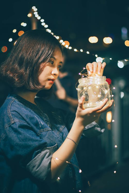 Photo of Woman Holding Jar With String Lights