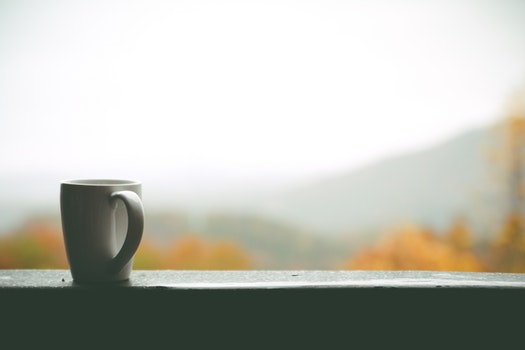 White Mug on Window over Looking Autumn Trees and Hills in Distance during Daytime