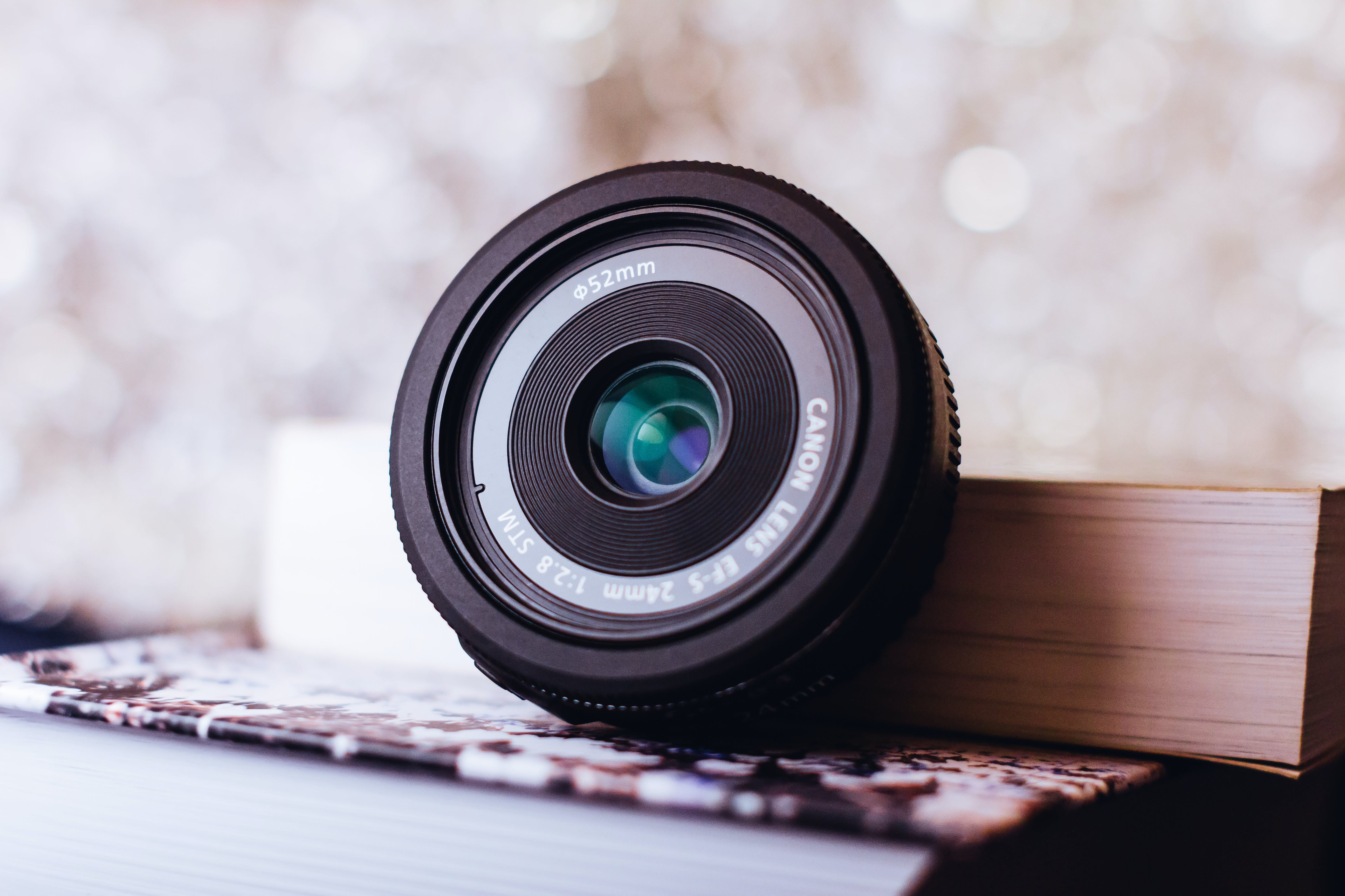 Black Canon Zoom Lens Leaning on Book