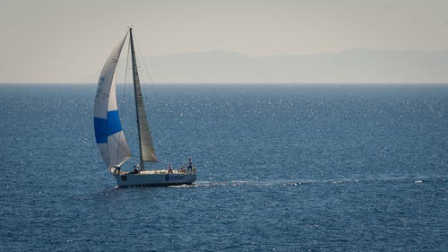 White and Blue Sailboat on Sea