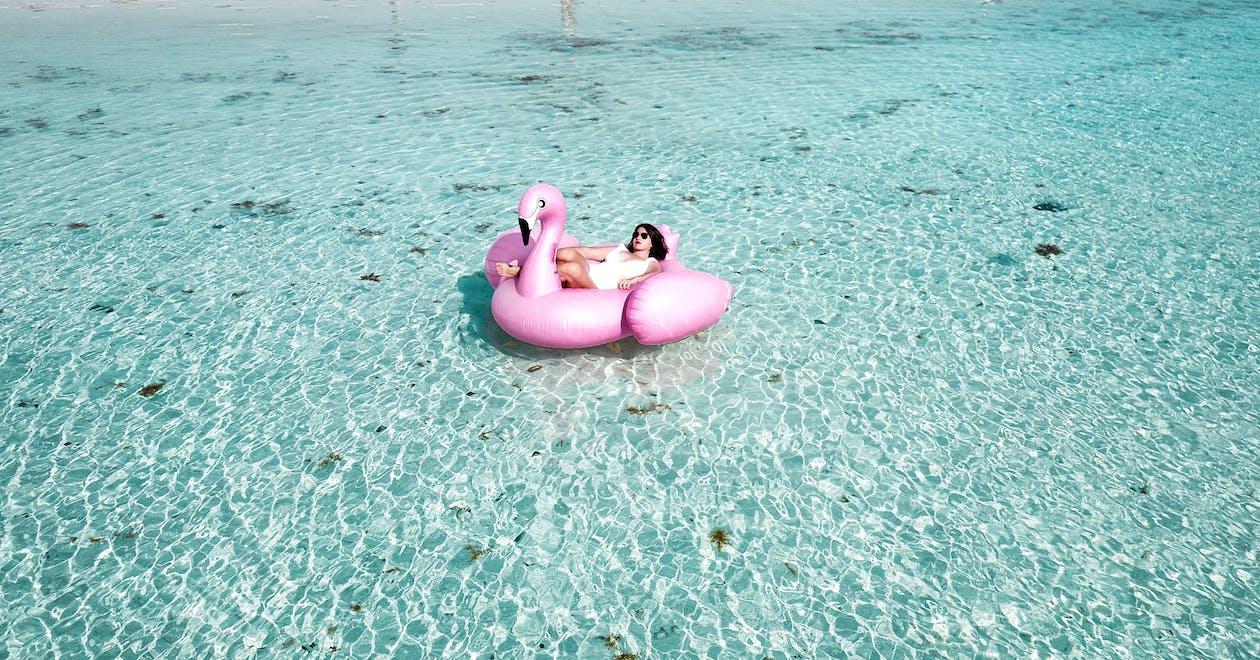 Mulher Deitada No Flamingo Bouy Rosa Em Um Corpo D'água