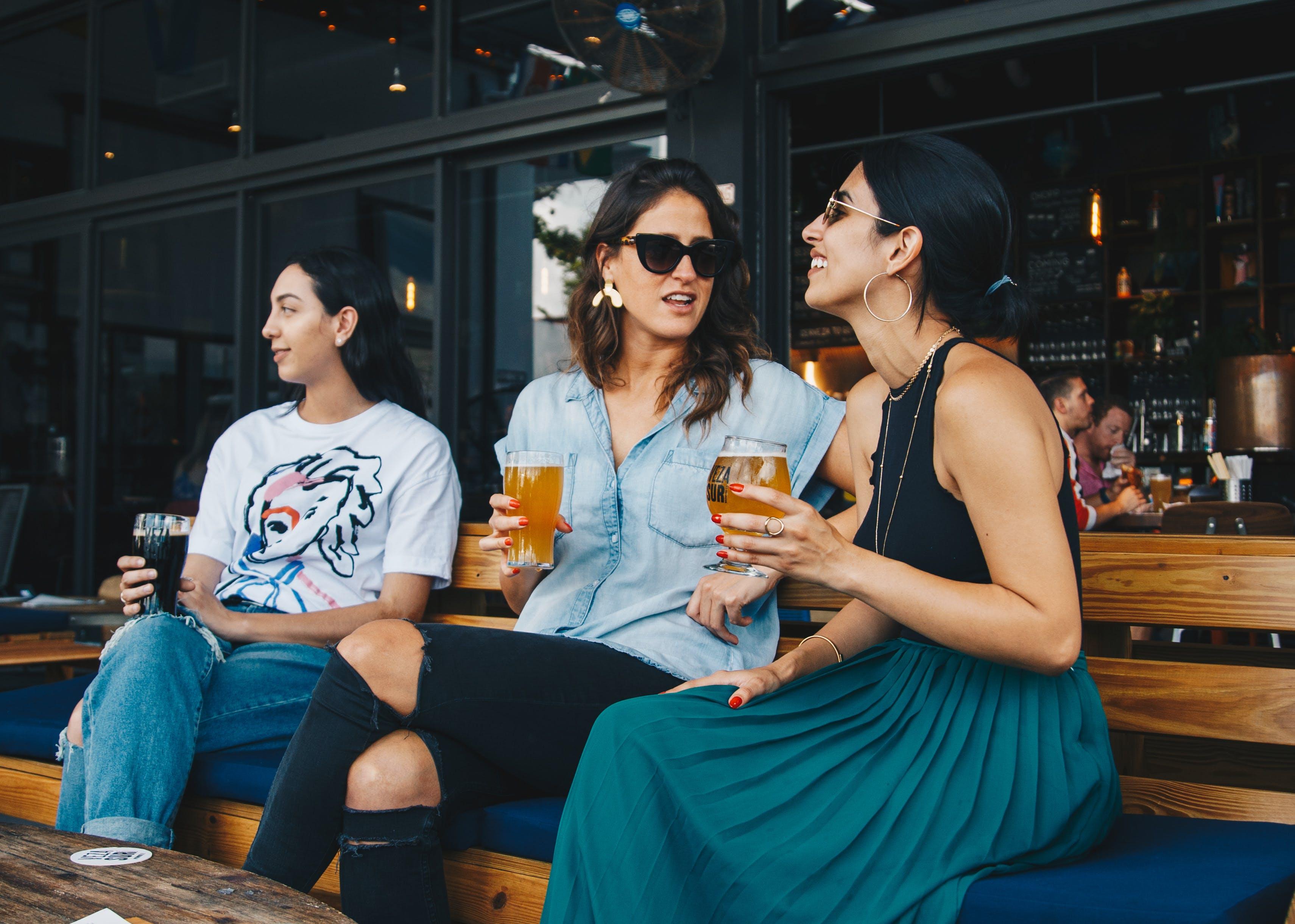 Three Women Holding Drinking Glasses