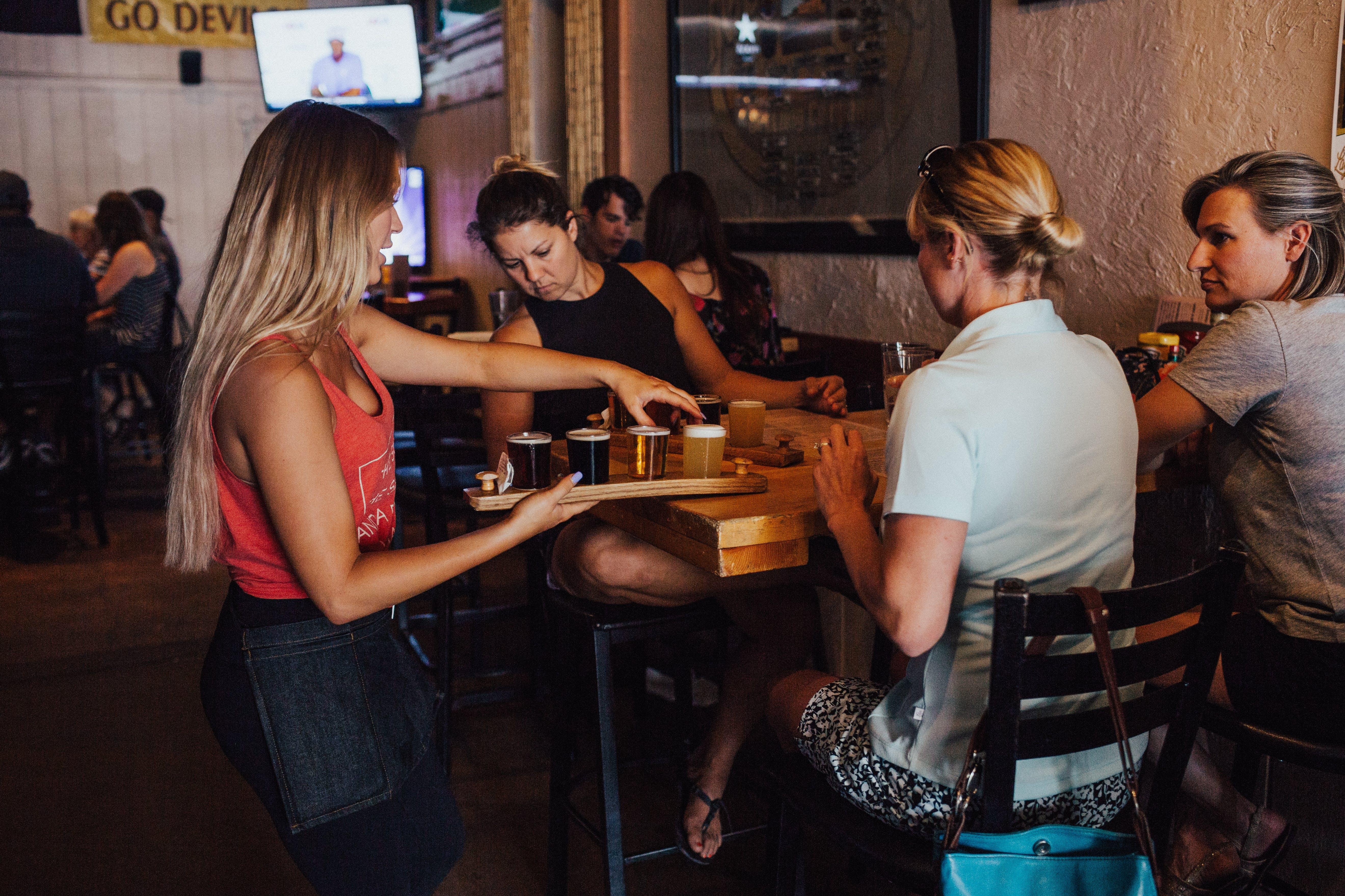 Woman Serving Drinks on Women Sitting Inside an Establishment