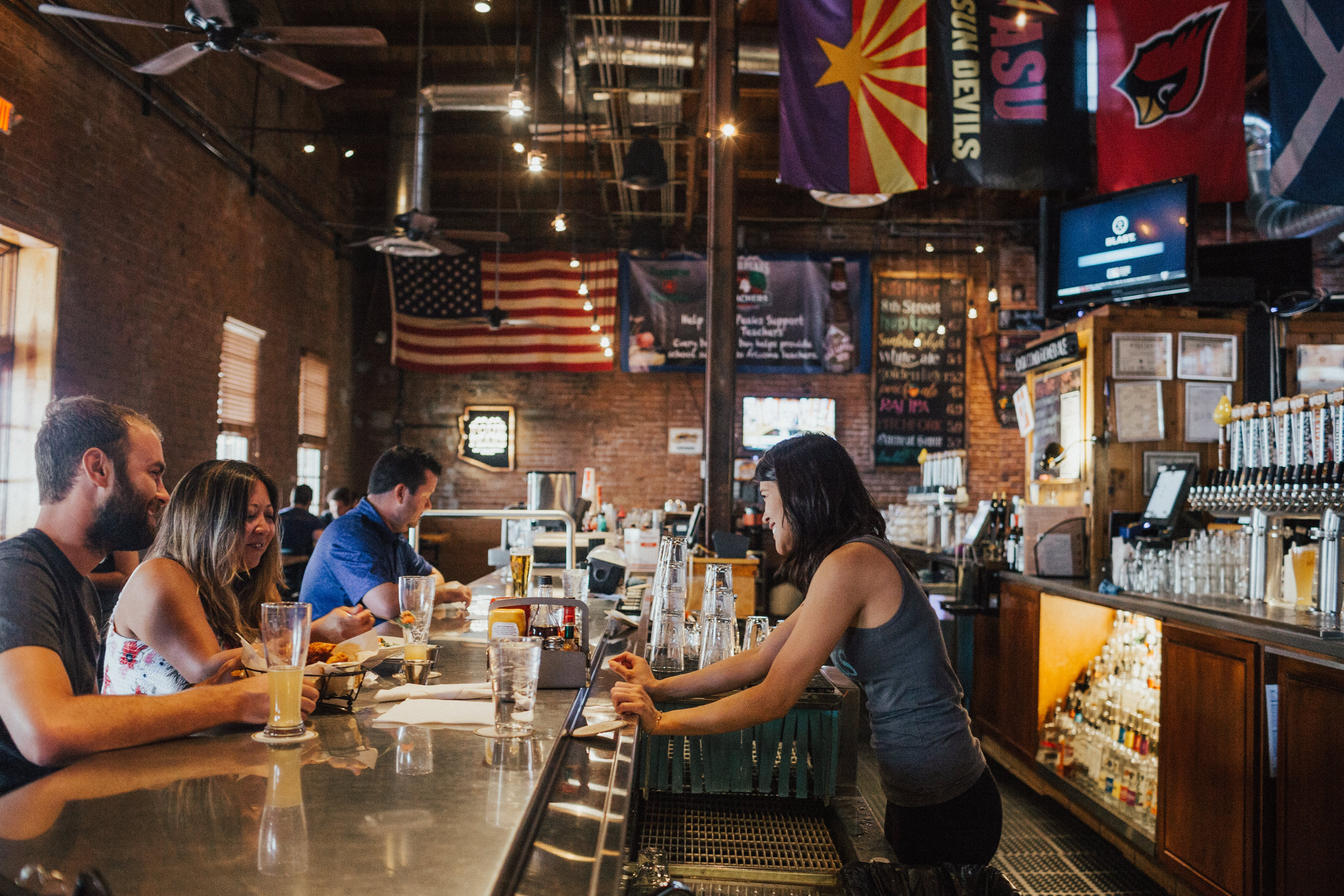 Woman Wearing Gray Tank Top in Bar Counter Attending Costumers