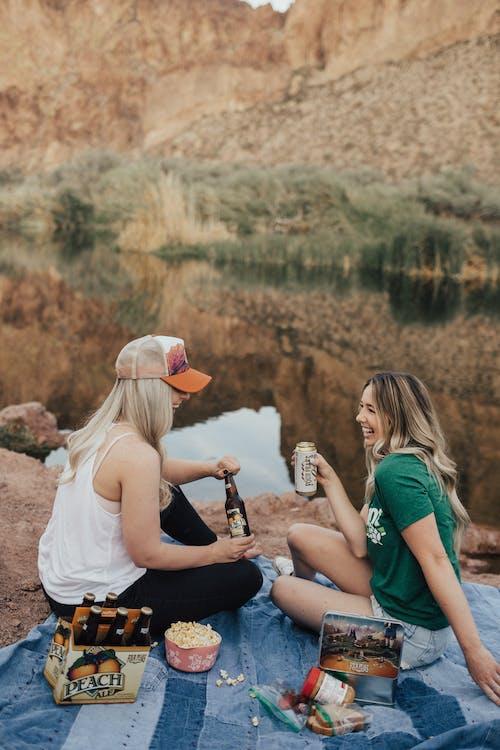 ピクニックで白いトップの女性の横に座っている緑のクルーネックtシャツの女性