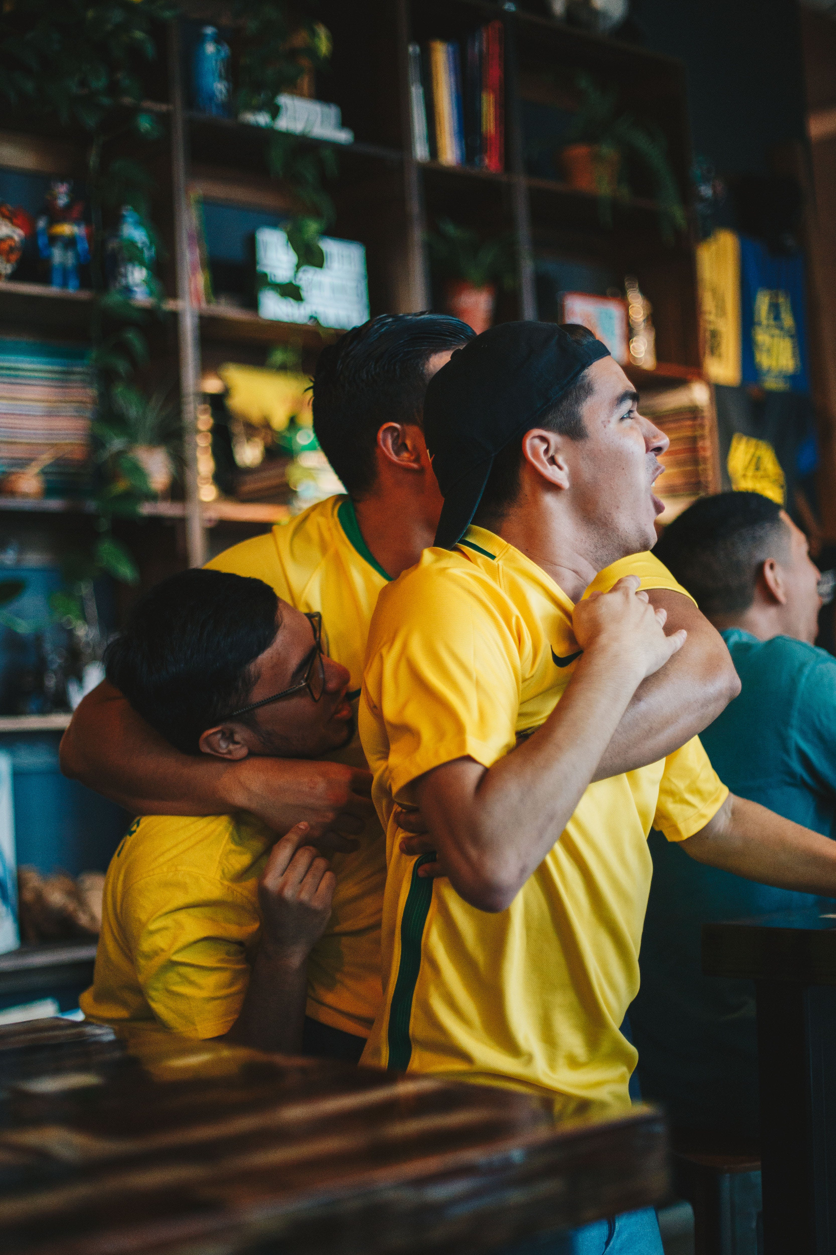 Three Men Wearing Yellow Shirt Embracing Each Other