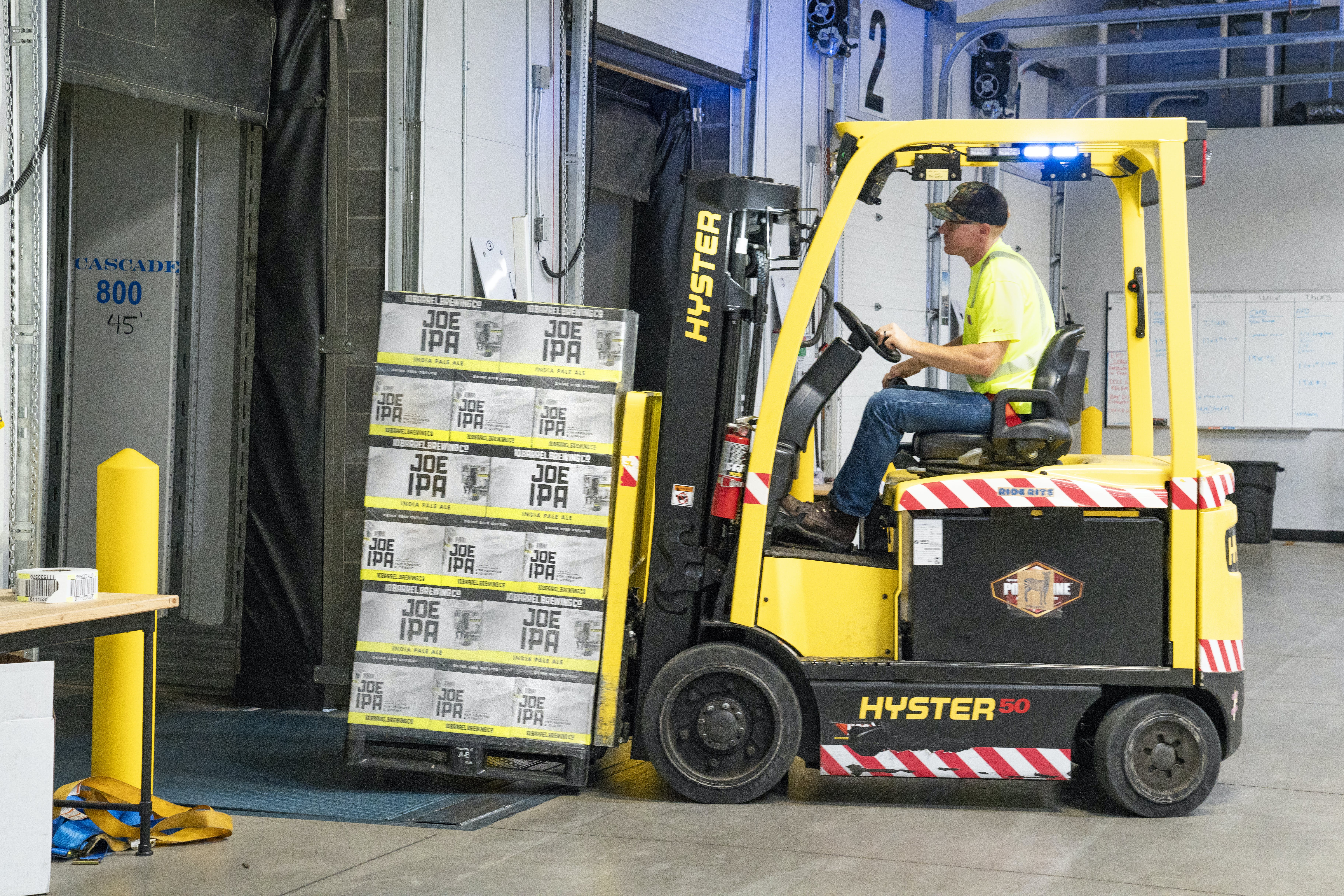 Man Riding a Yellow Forklift With Boxes