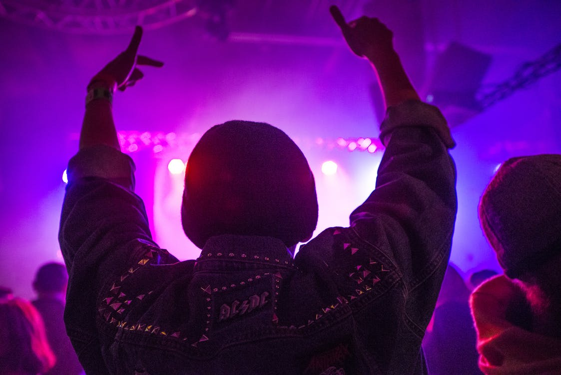 Back of Man Raising Hands Inside Room Full of People With Purple Lights