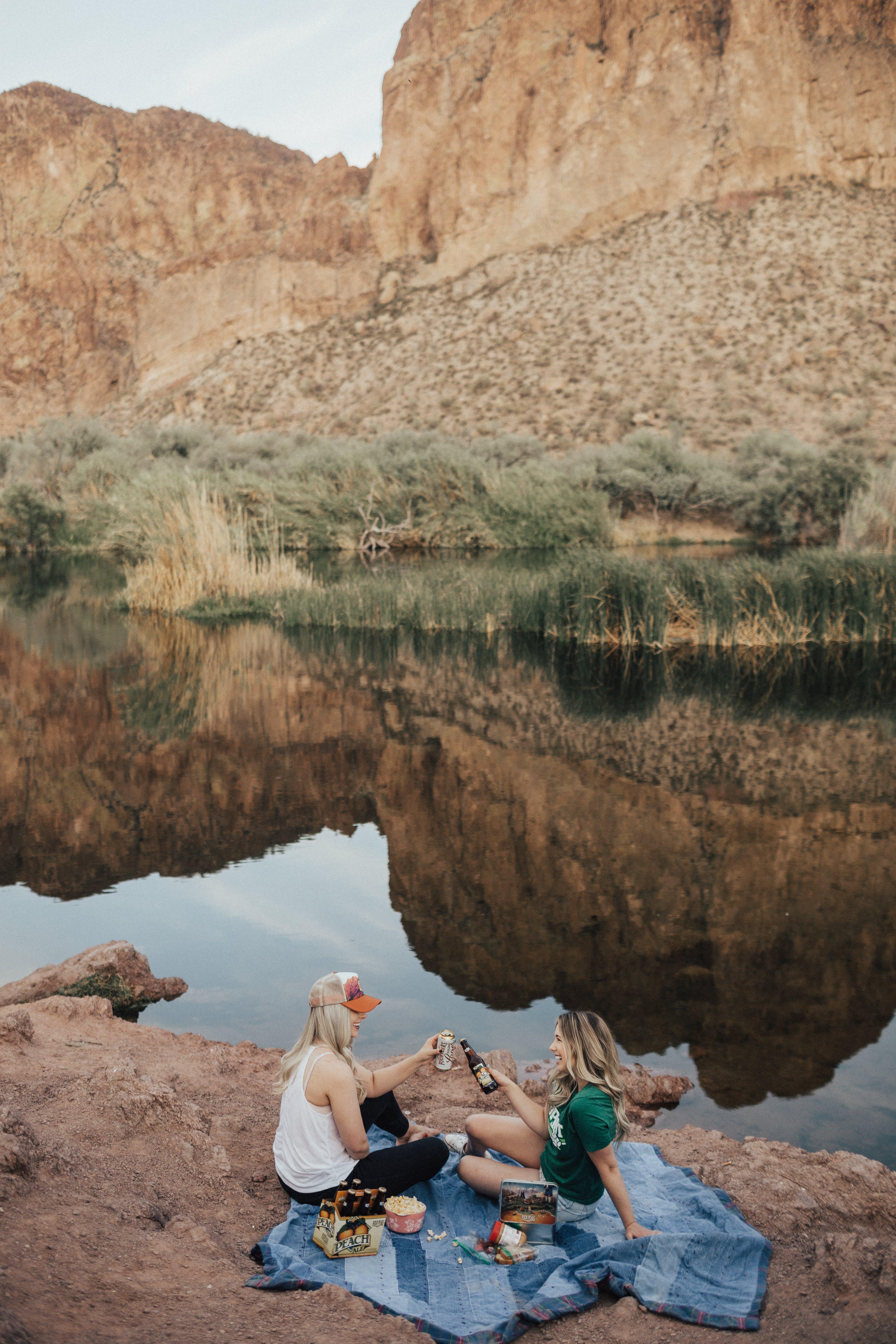 Two Woman Sitting Near Body of Water