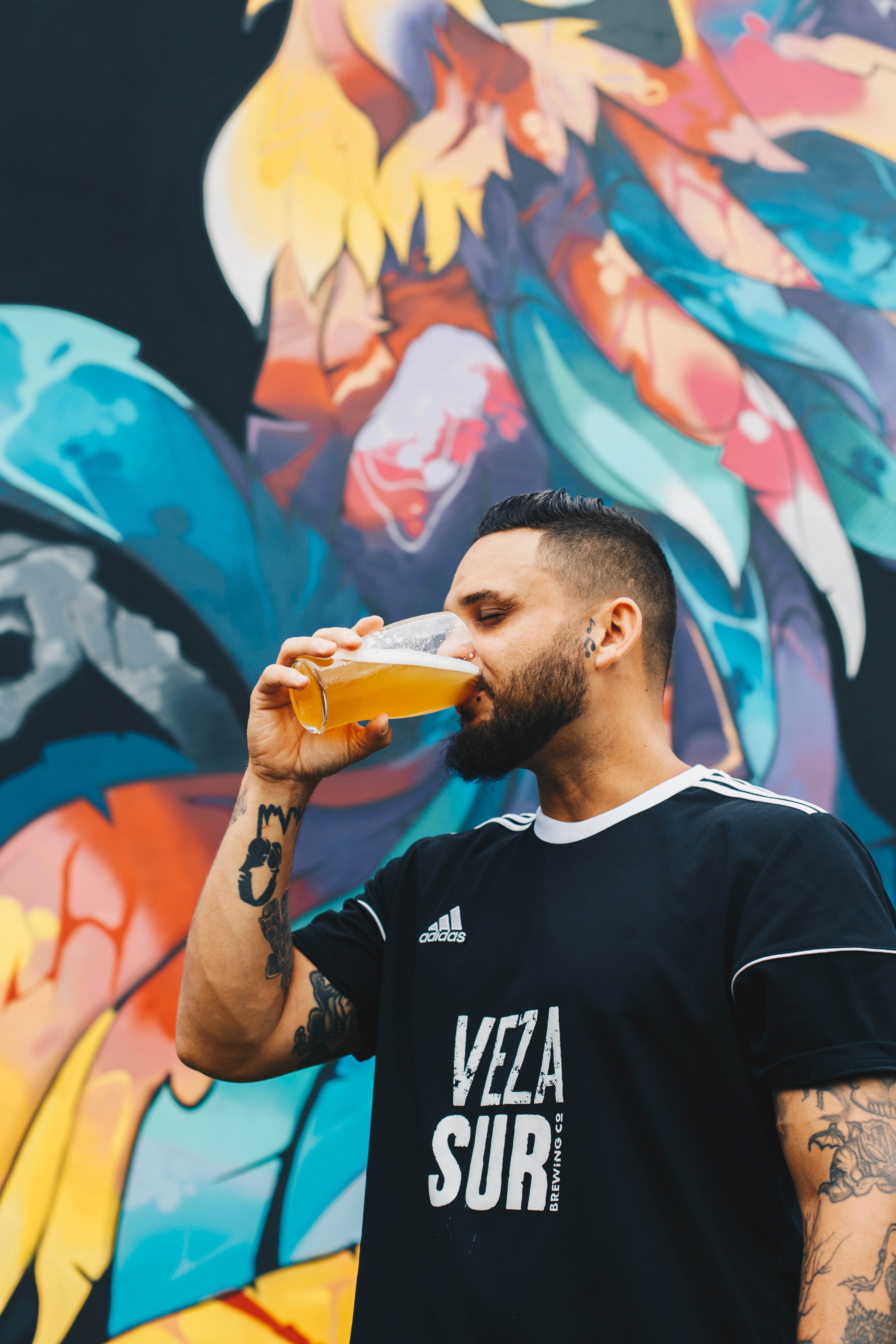 Tattooed Man Drinking on Clear Drinking Glass in Front of Multicolored Painted Wall
