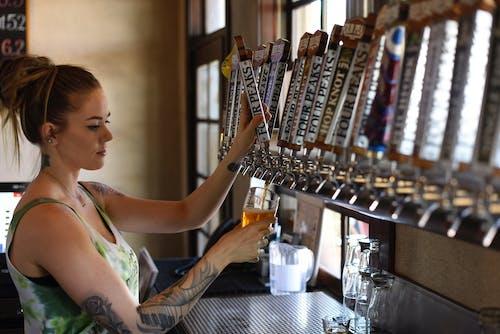 Woman Holding Beer Tap Handle and Pilsner Mug