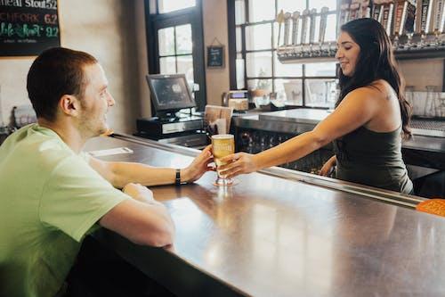 Woman Handing Glass Cap to Man in Green T-shirt