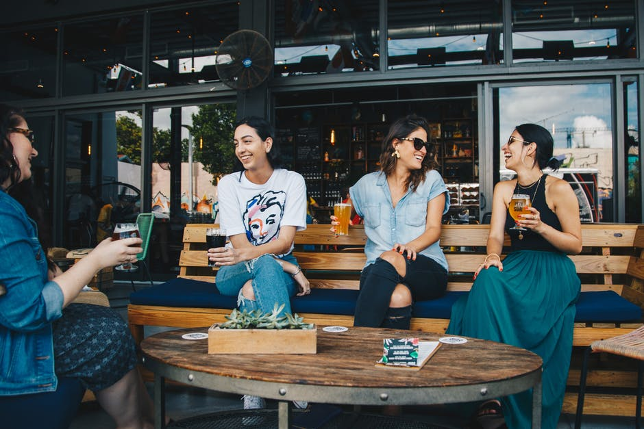 Four Women Sitting on Bench in Storefront While Drinking Alcoholic Beverages