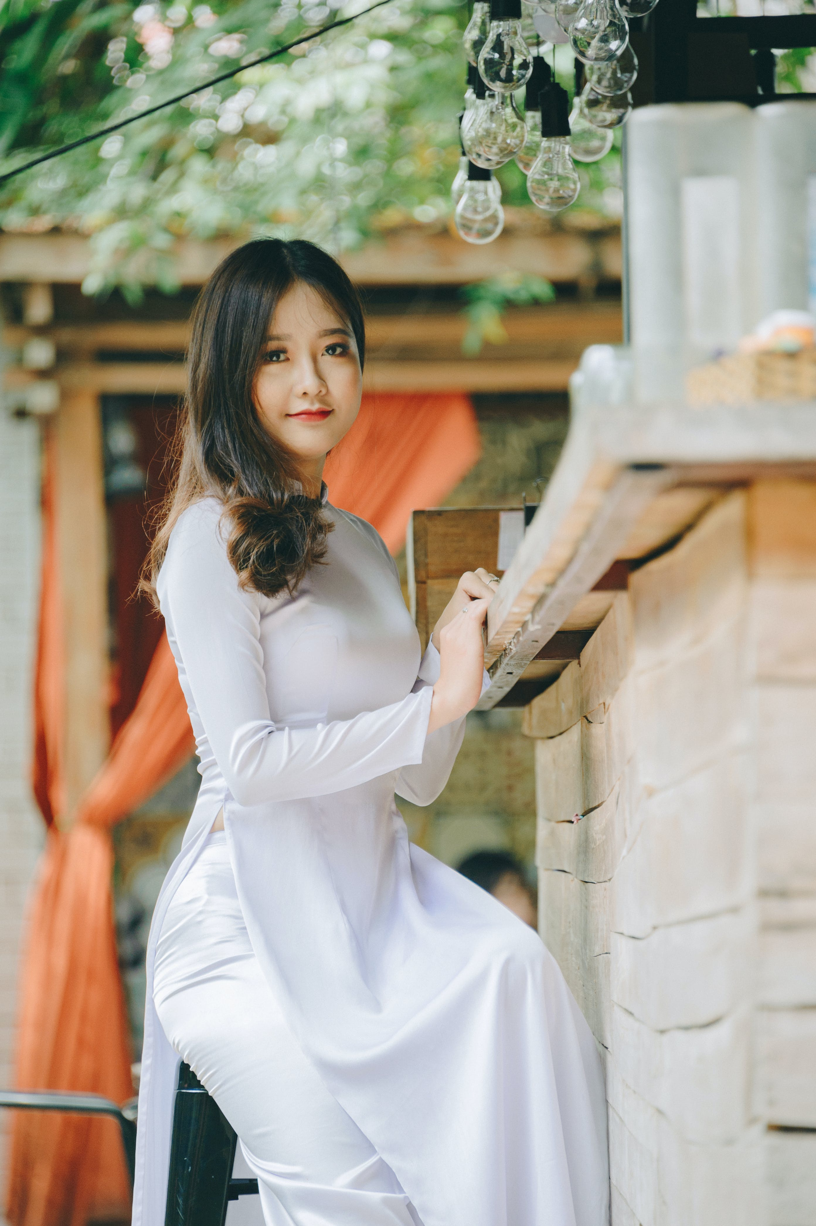 Woman Wearing White Dress Sitting on White Chair Smiling While Taking Picture
