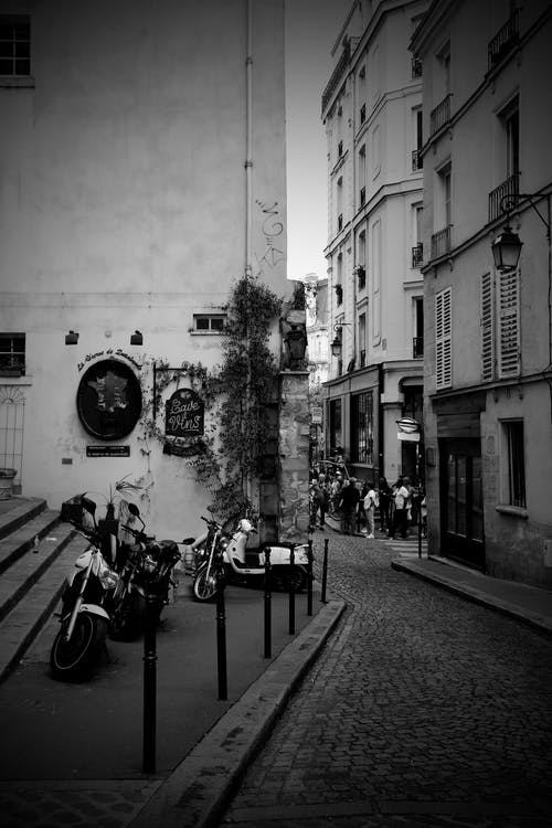 Grayscale Photo of Buildings With Motorcycle Beside