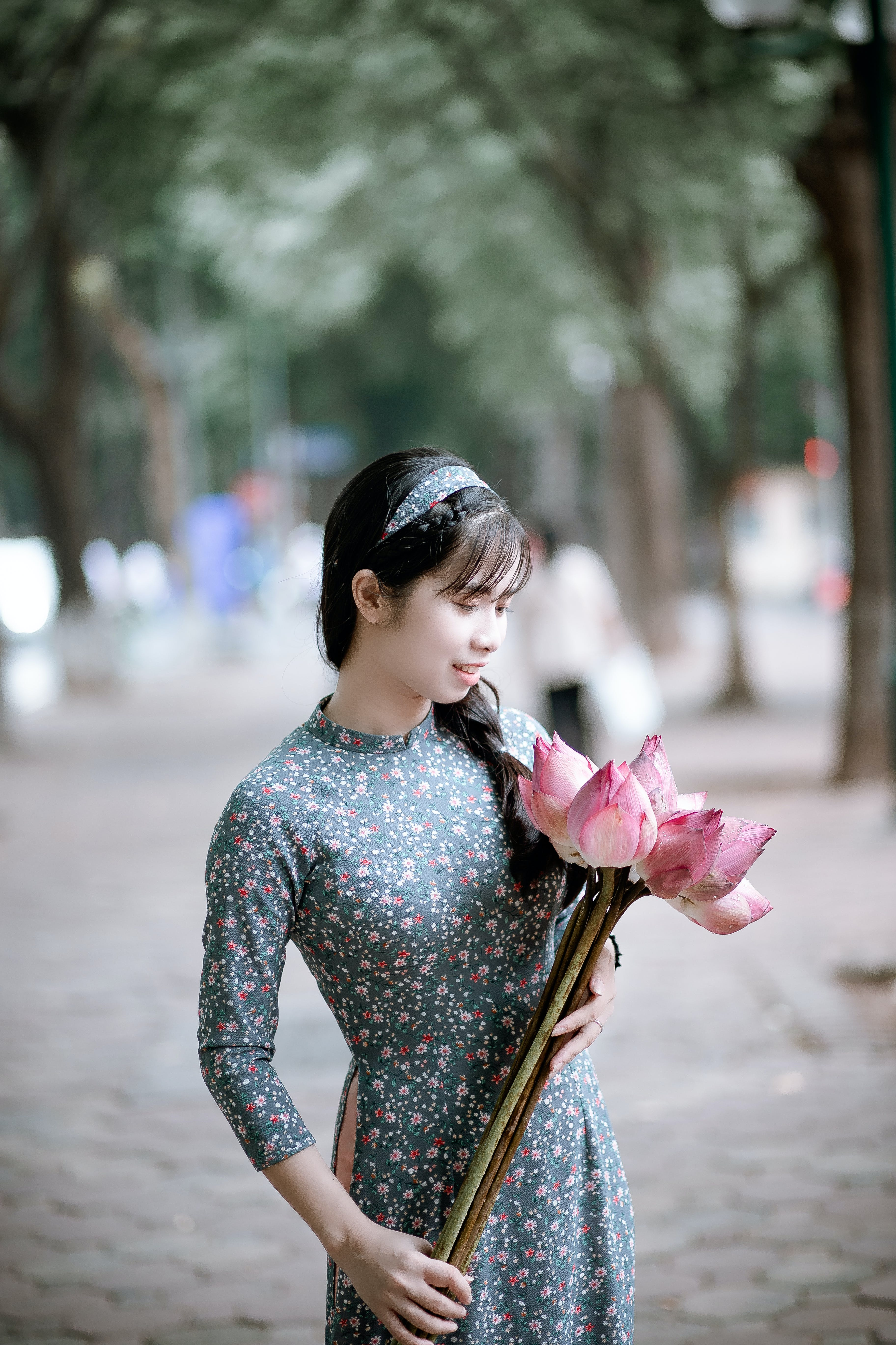 Woman Holding Pink Lotus Flowers Bouquet on Road Beside Green Trees