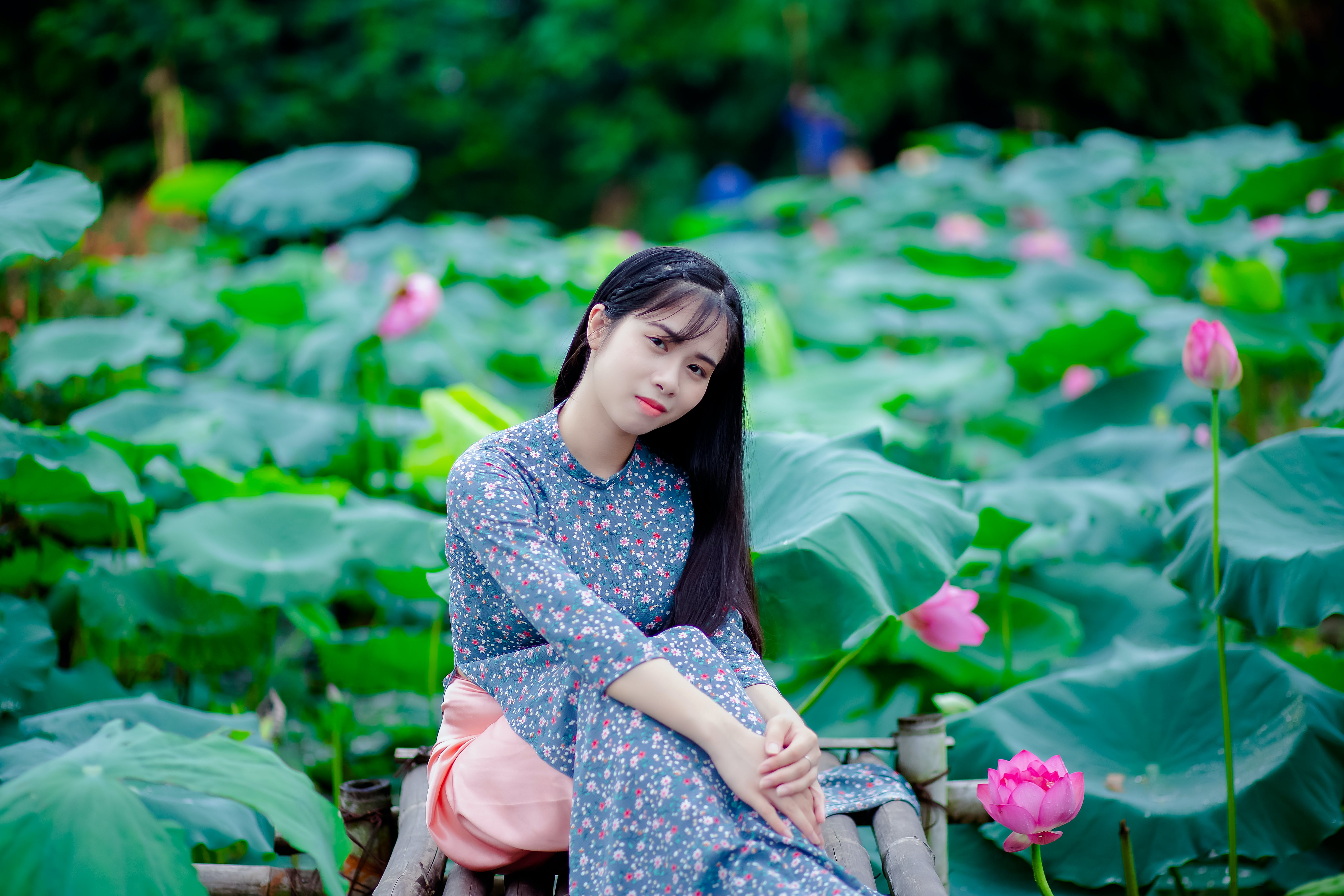 Woman Sitting on Brown Chair Surrounded With Lotus Flowers