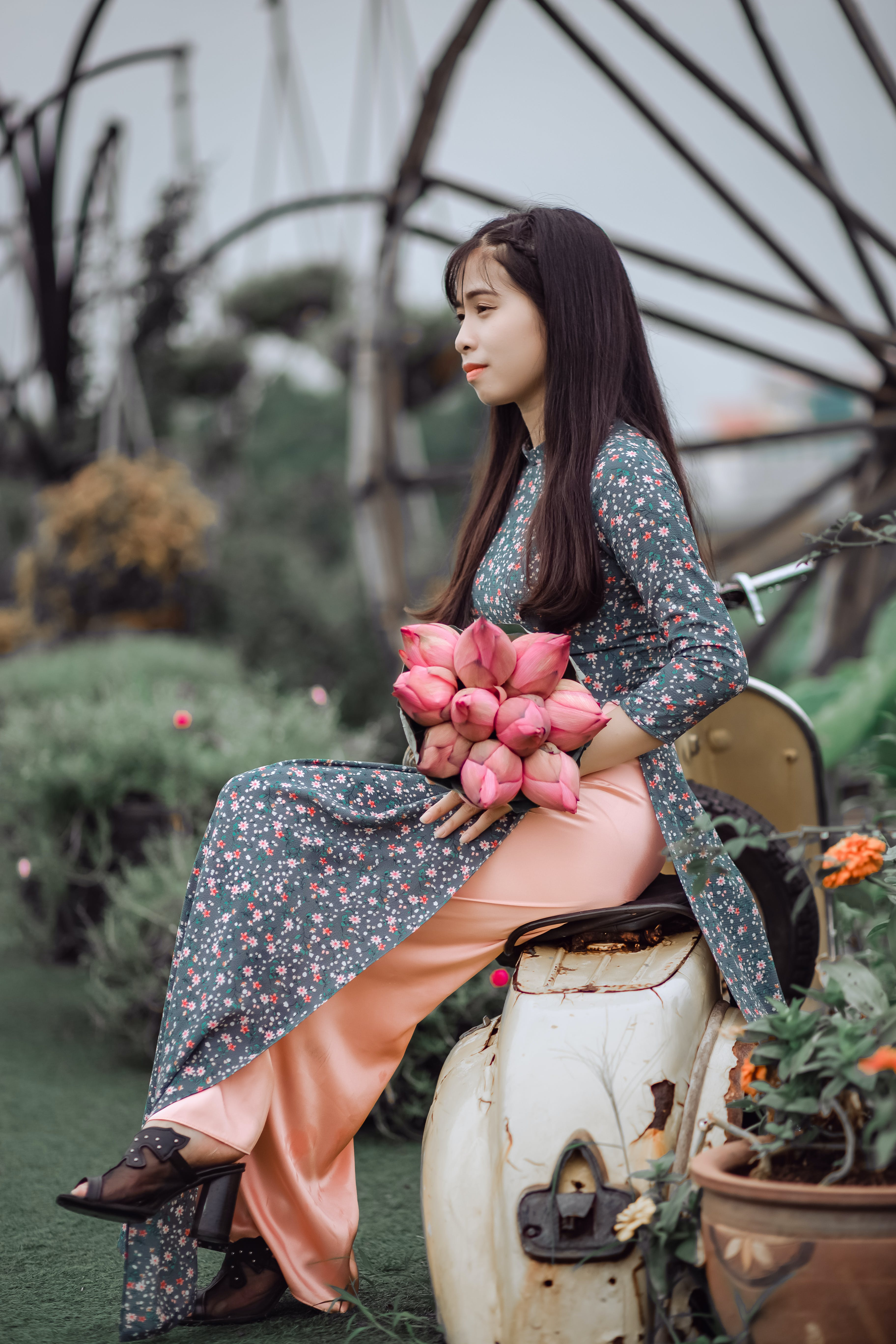 Woman Sitting on Motorcycle While Holding Banana Blossoms Bouquet