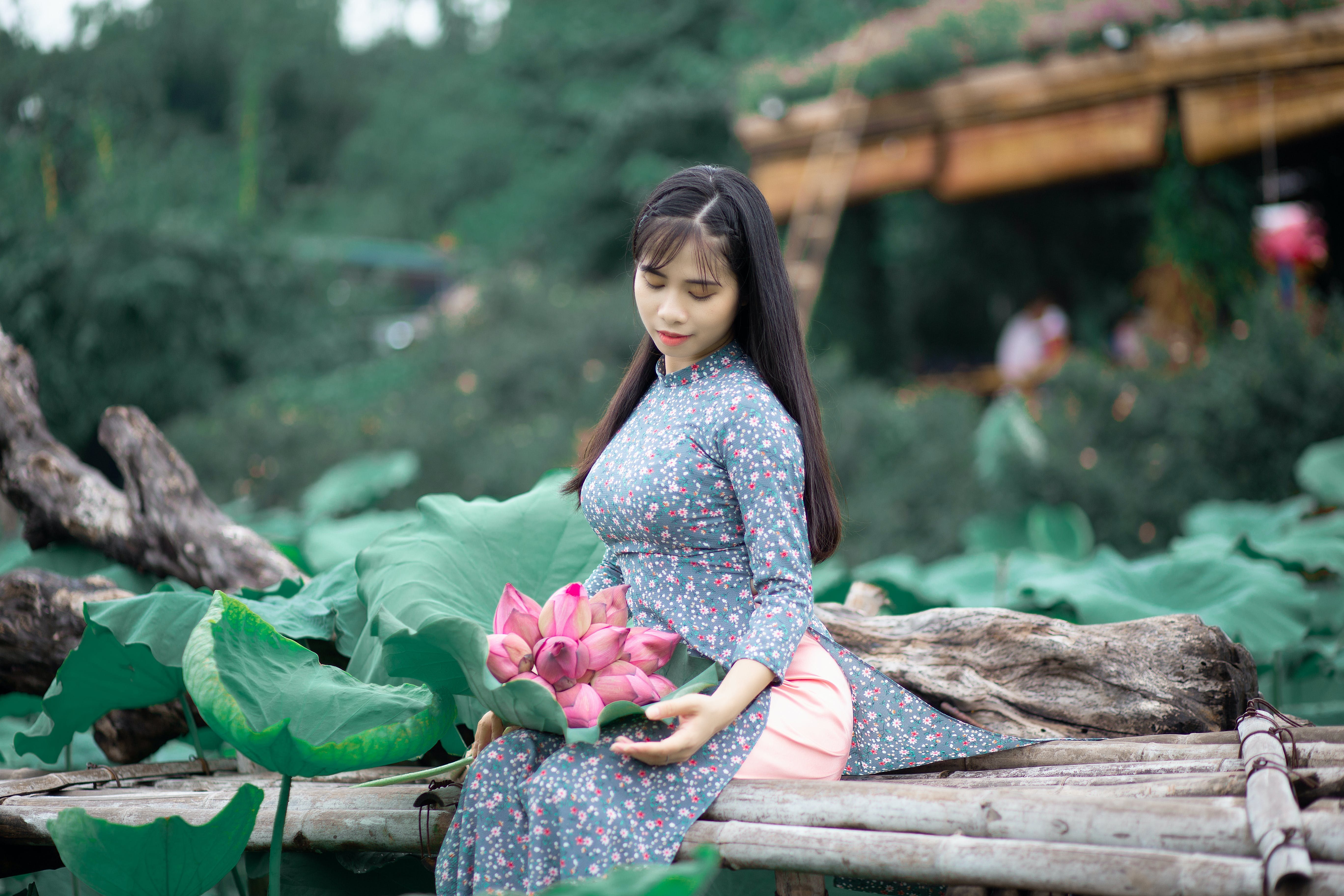Woman Sitting on Bamboo Bench With Bouquet of Pink Flowers on Laps