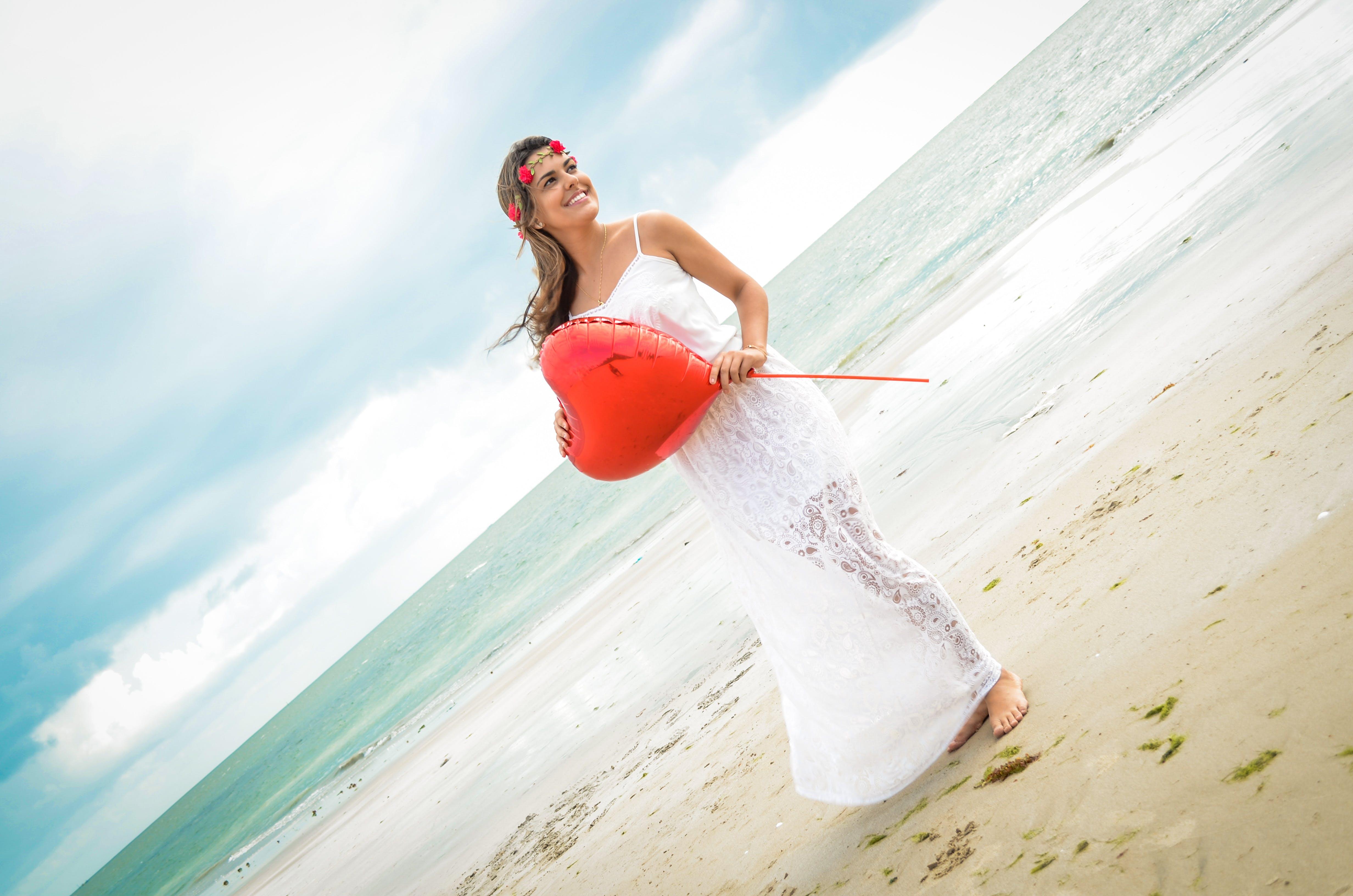 Woman Holding a Heart-shaped Balloon Standing on Seashore