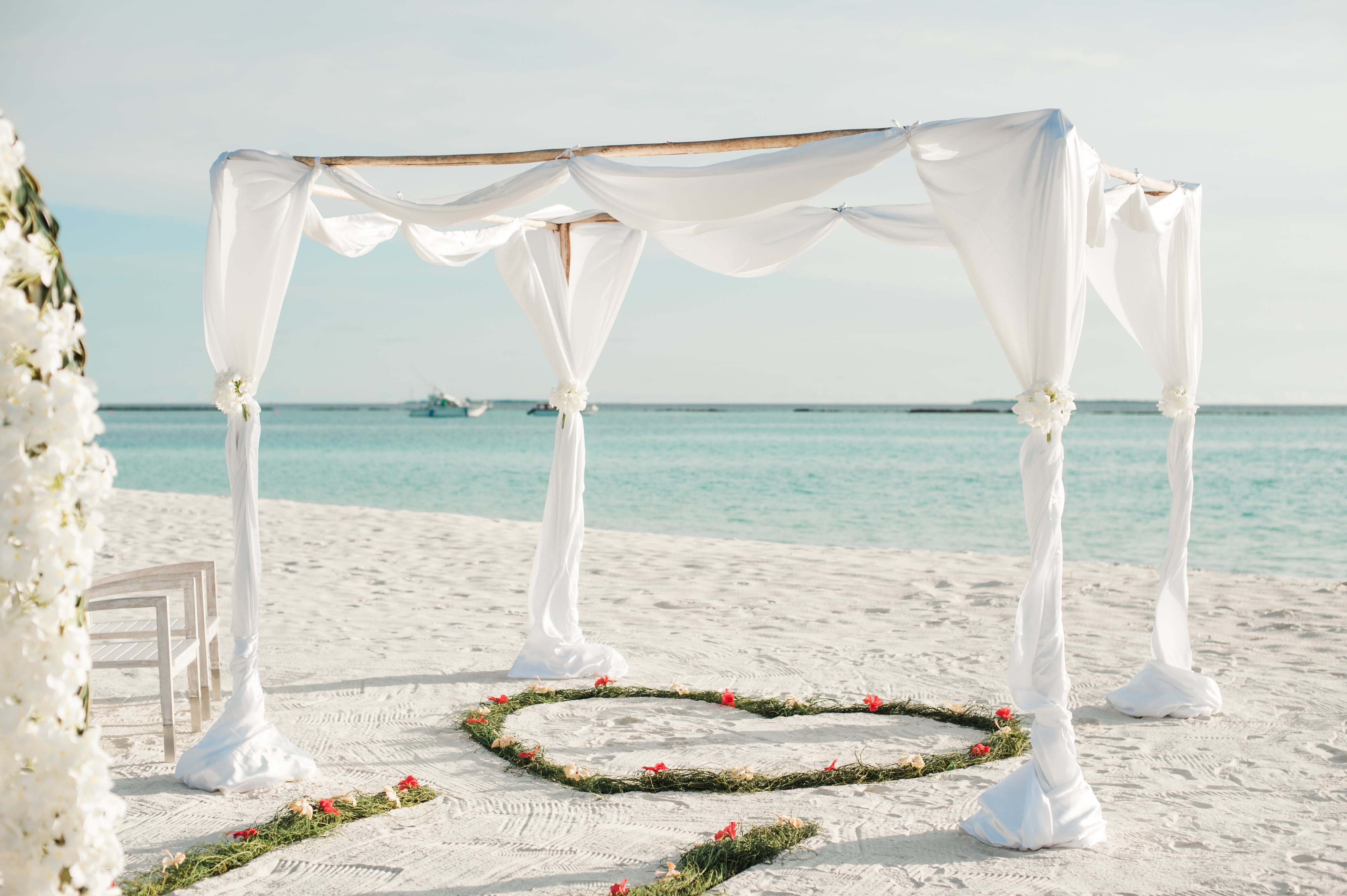 White Fabric Canopy Tent With Green Heart Floor Decor at Beach