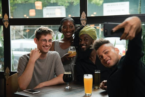 Happy multiethnic friends taking selfie on smartphone in cafe
