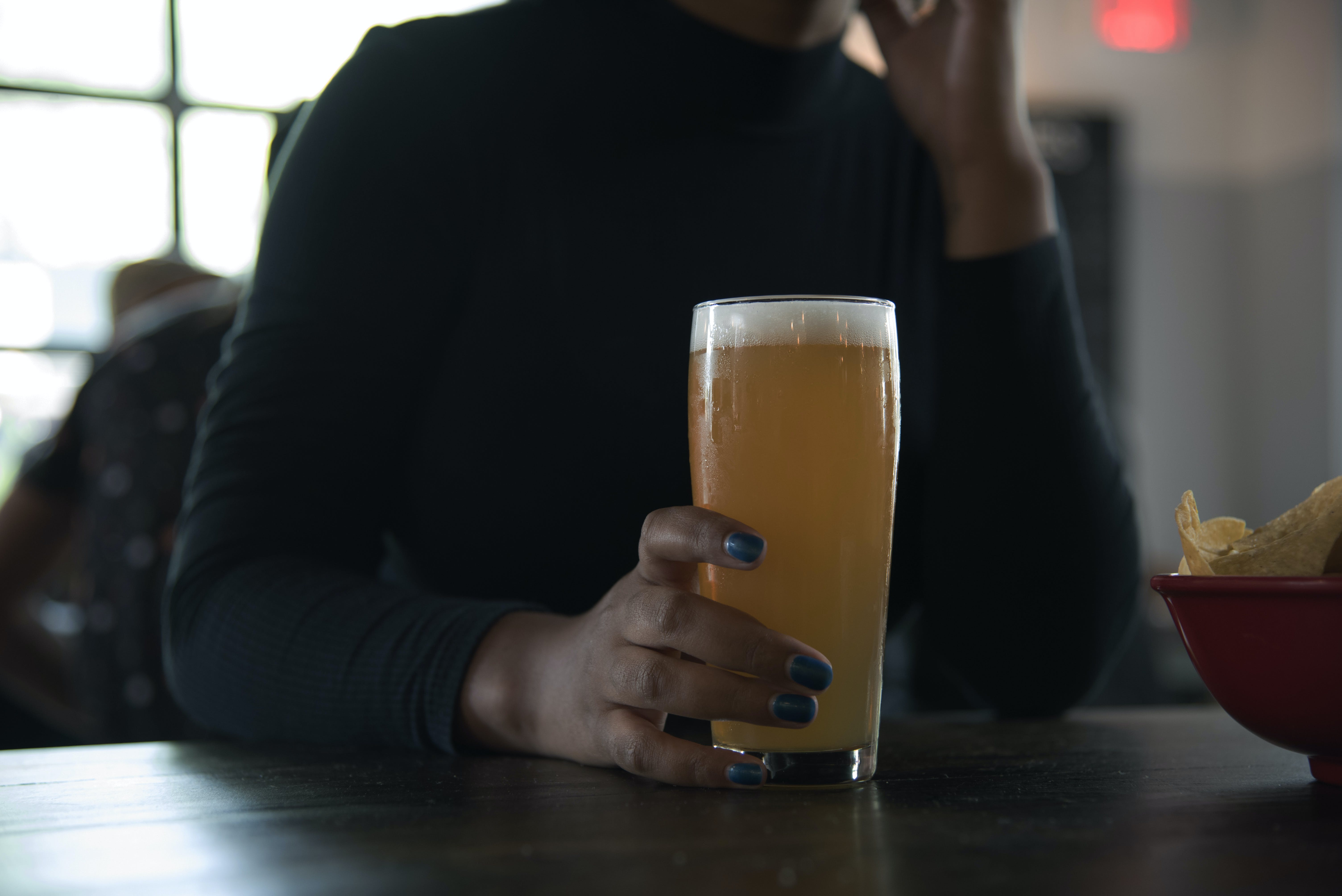 Person Holding Drinking Glass With Orange Liquid