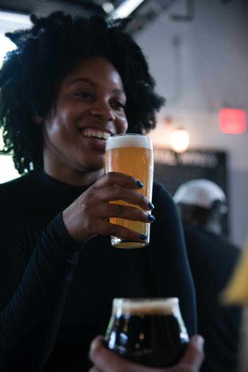 Cheerful black woman with beer in pub