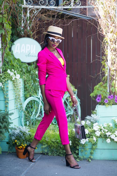 Woman in Pink Suit Walking Near Garden