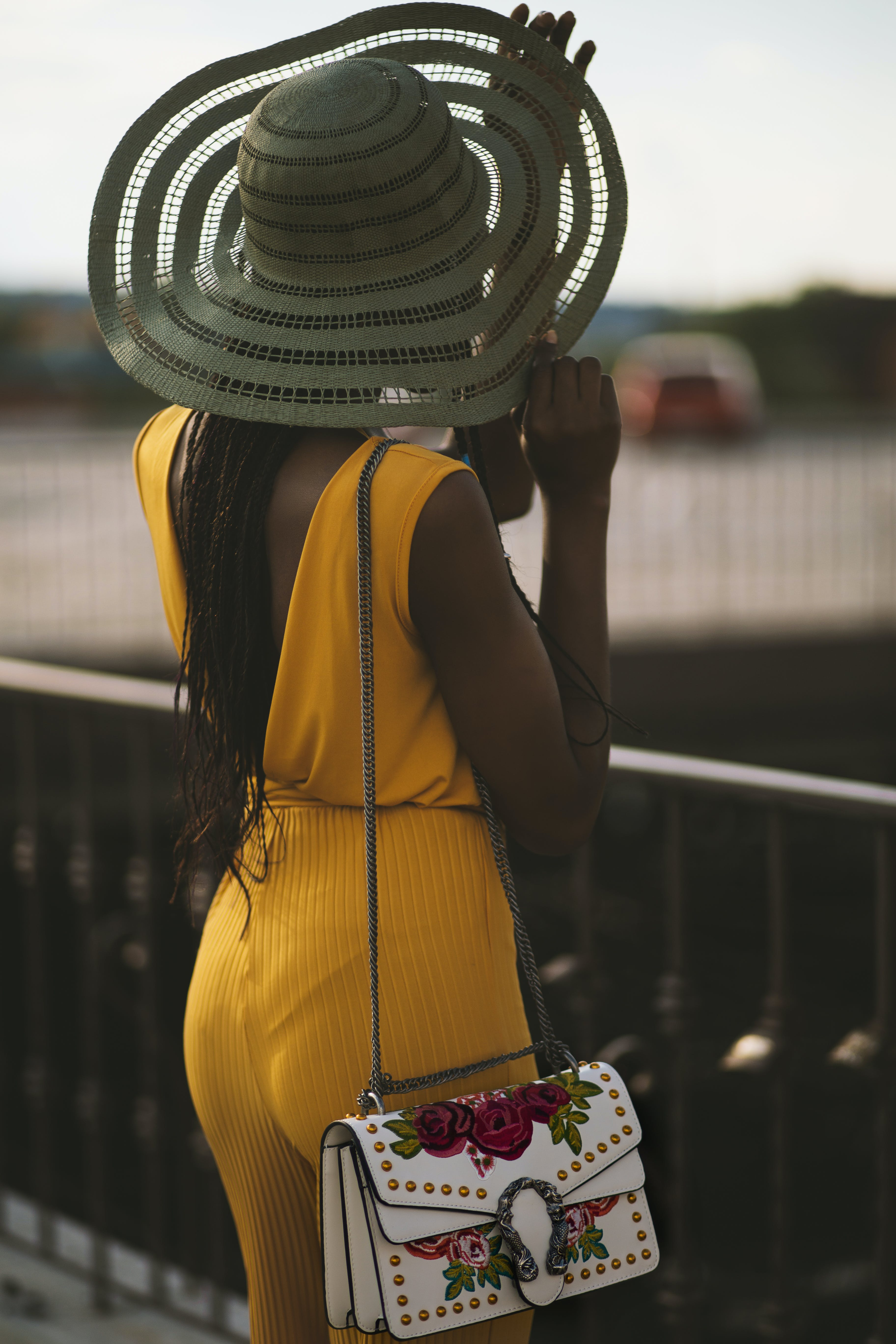 Woman Wearing Fascinator Hat and Yellow Jumpsuit