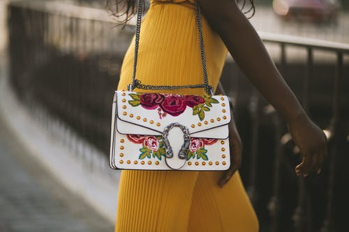 Person Carrying White and Red Floral Leather Crossbody Bag