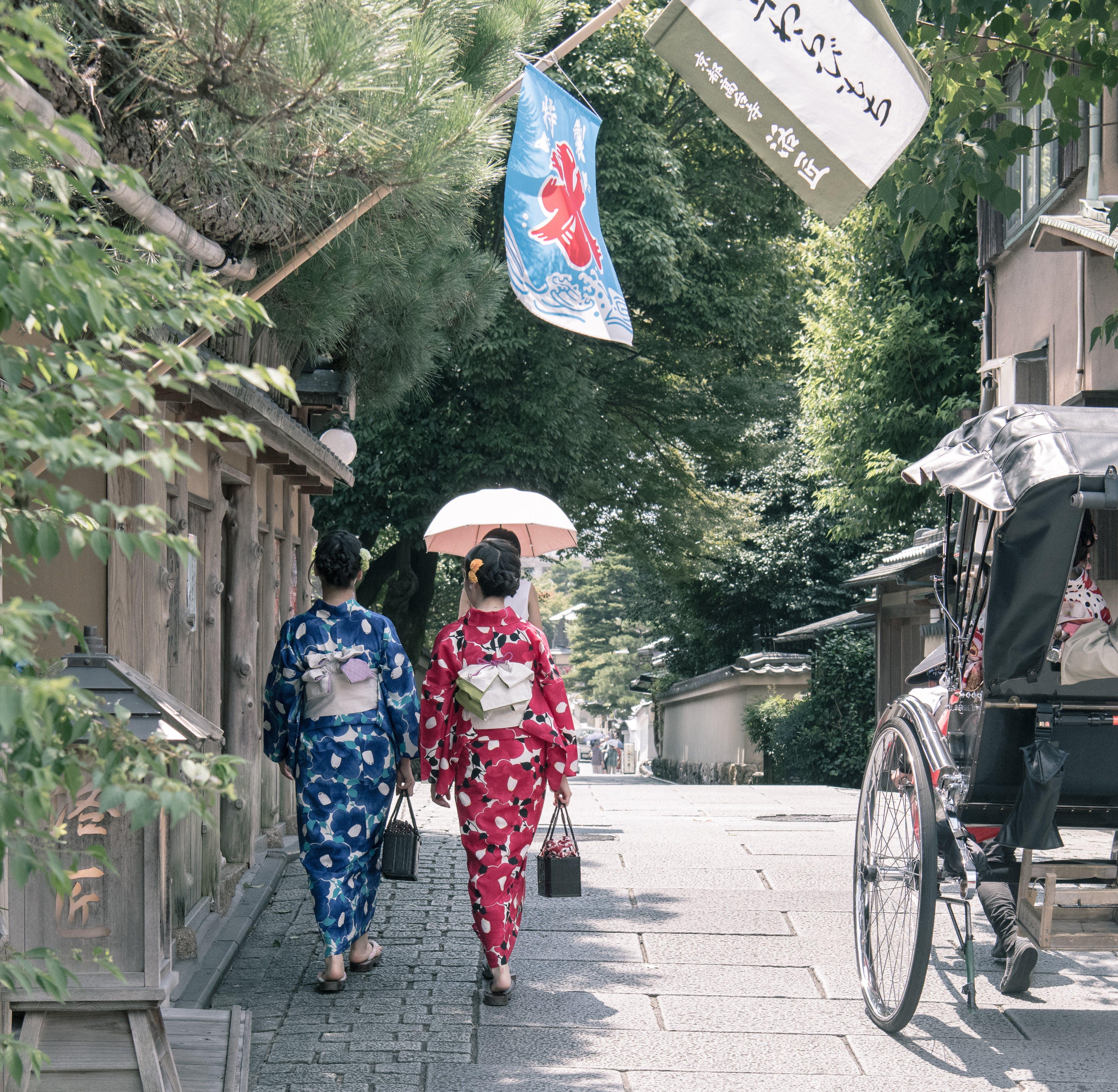 Two Woman Wearing Kimono Dress Walking Beside Sidewalk