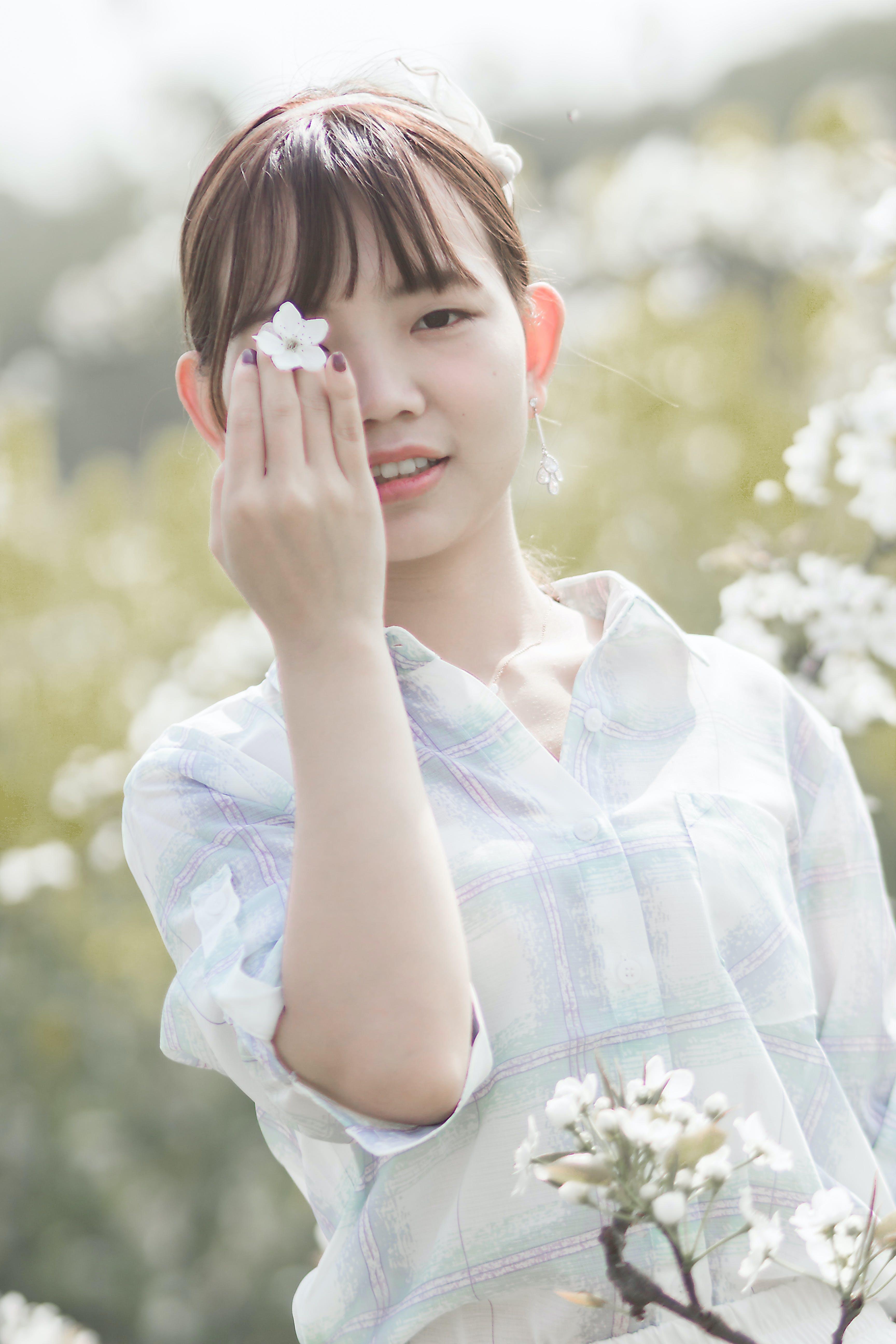 Woman Holding White Cherry Blossom Flower