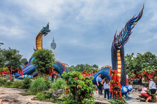 People Roaming Around Near Blue Dragon Monument