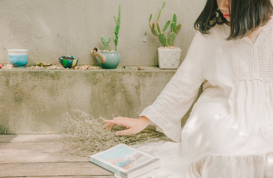 Woman Holding Dried Flowers Beside Book While Sitting