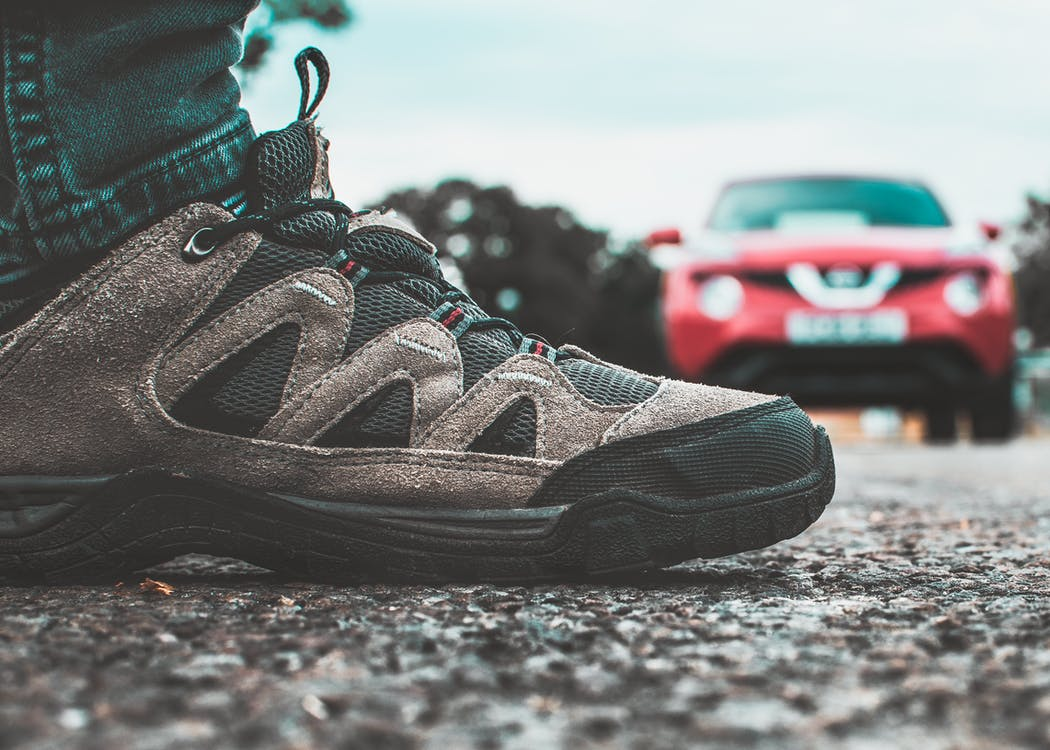 Sepatu Hitam Dan Abu Abu Dekat Kendaraan Merah
