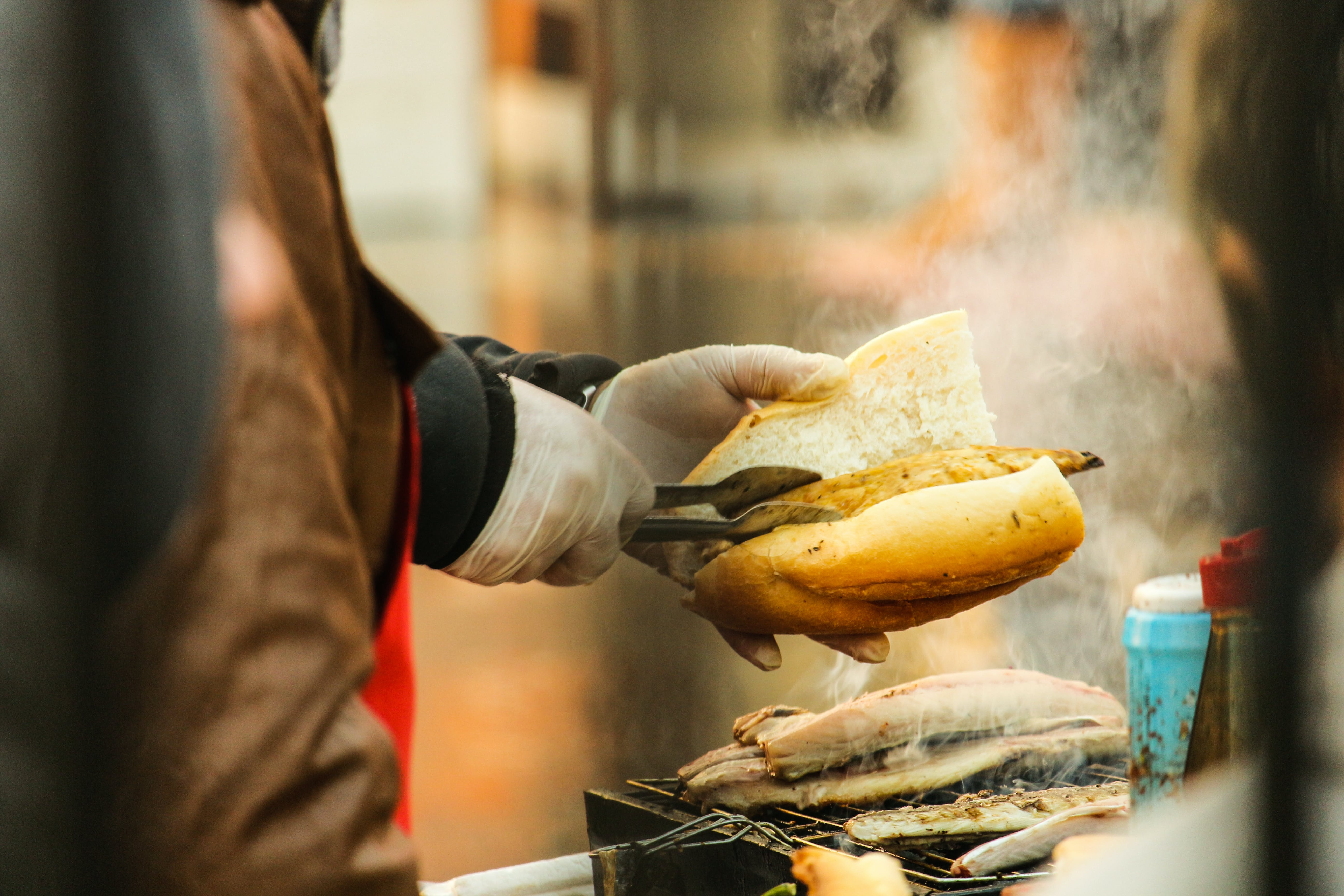 Person Putting Grilled Food in Sliced Bread