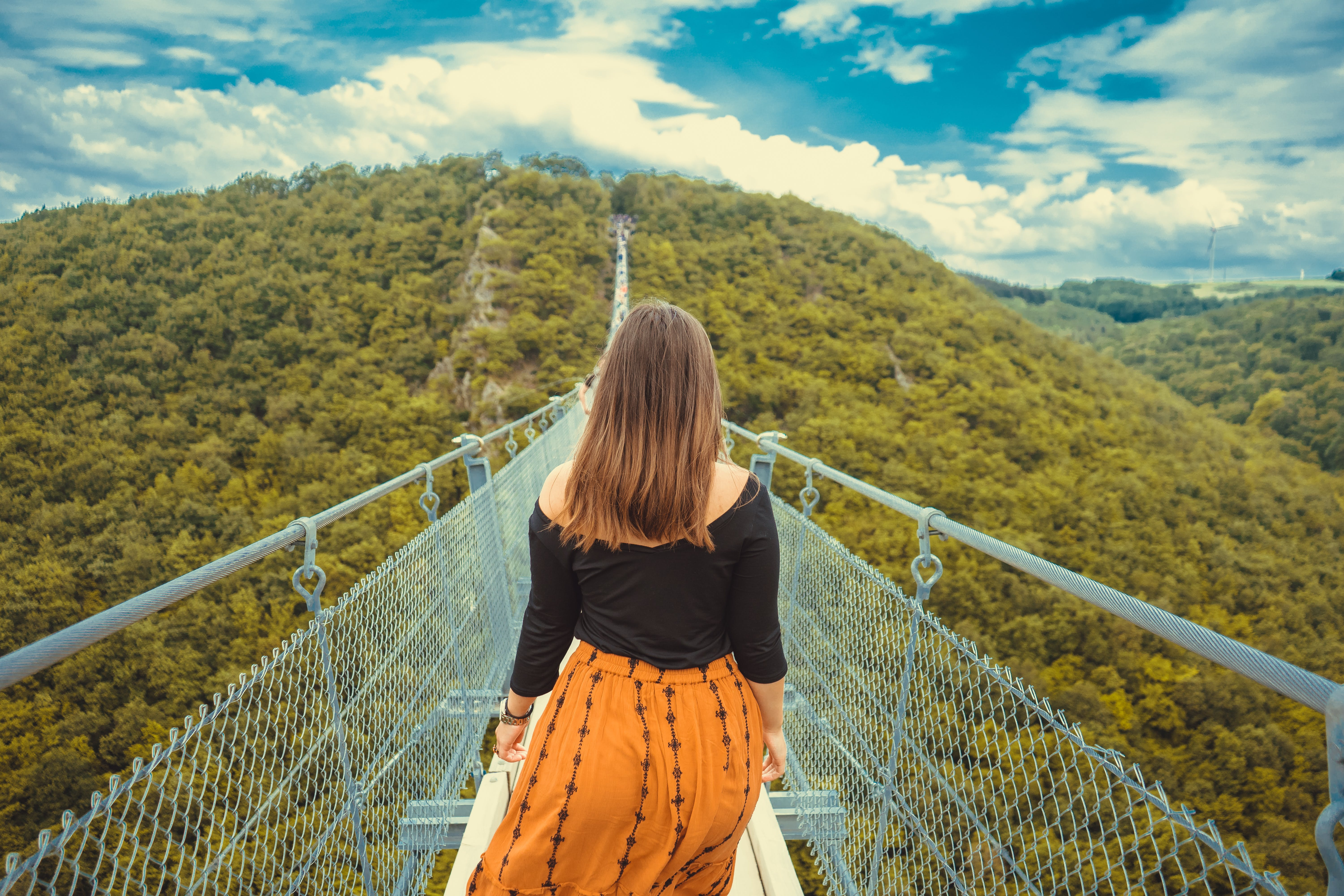 Photo of Woman Walking on a Canopy Walkway.