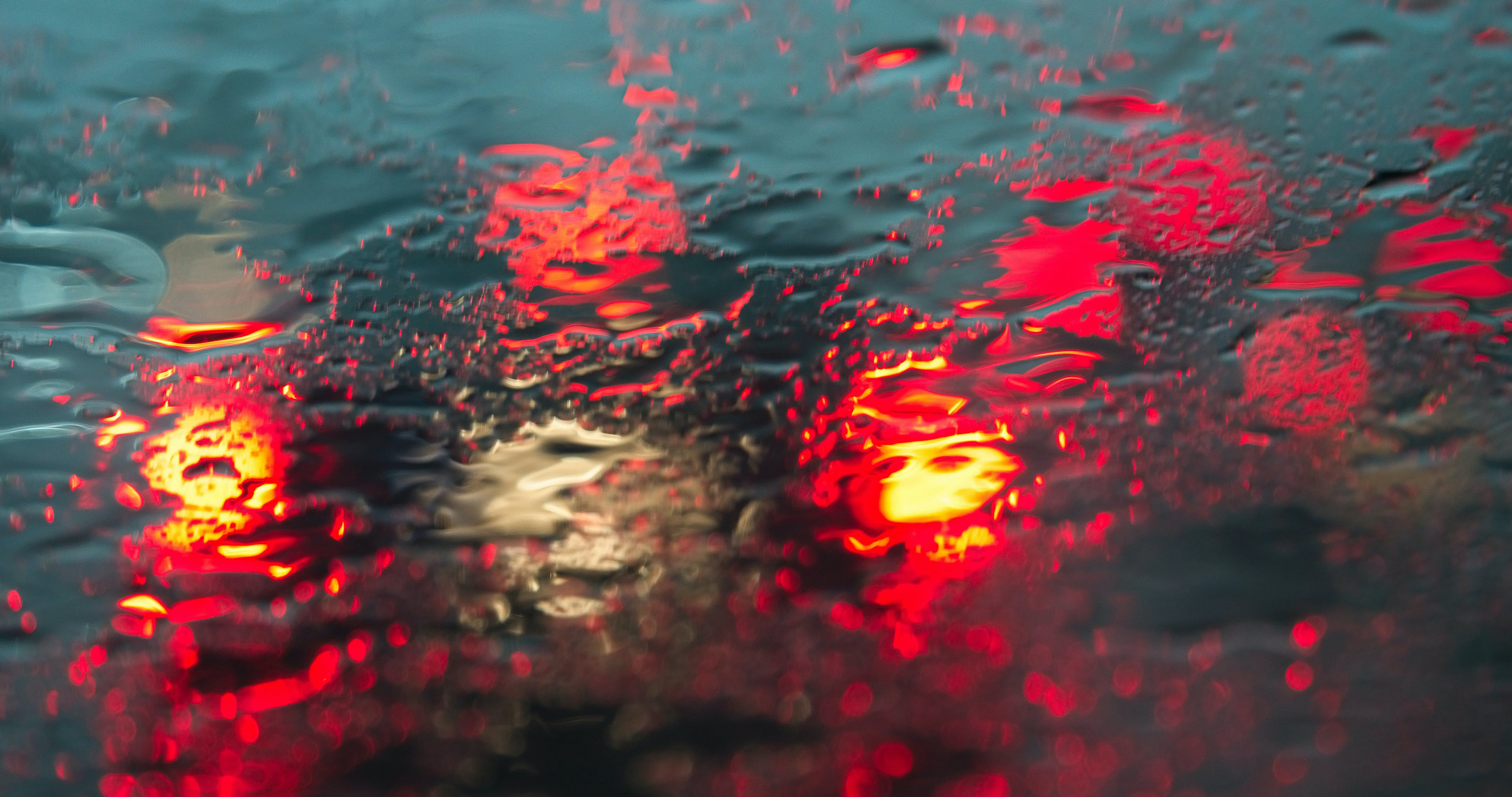 Clear Glass Covered in Water With Ray of Red Lights