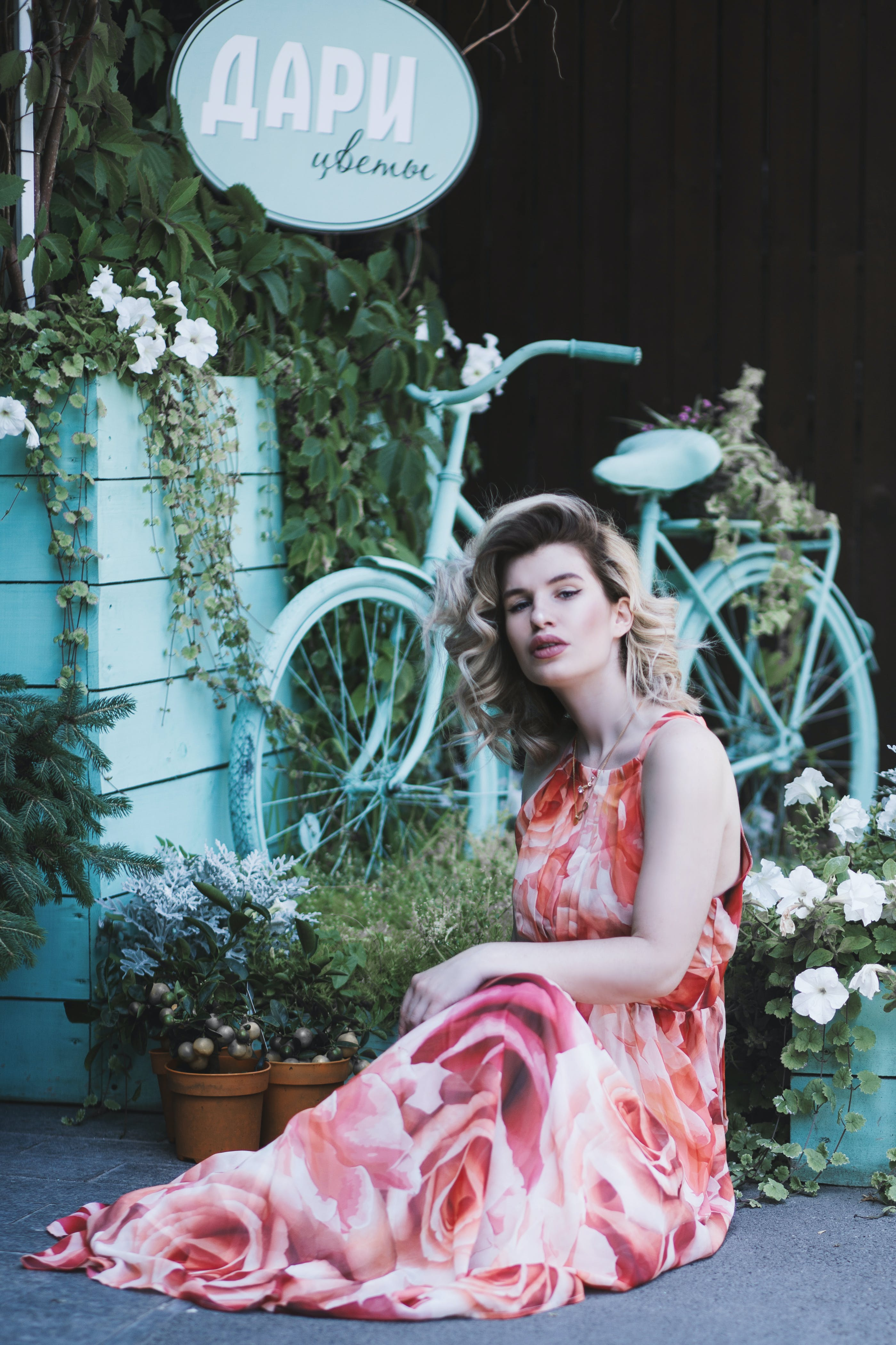 Woman in Floral Dress Sitting Near Plants and Bicylce