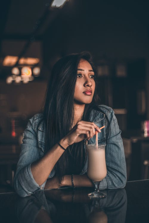 Woman Leaning on Table Having A Drink