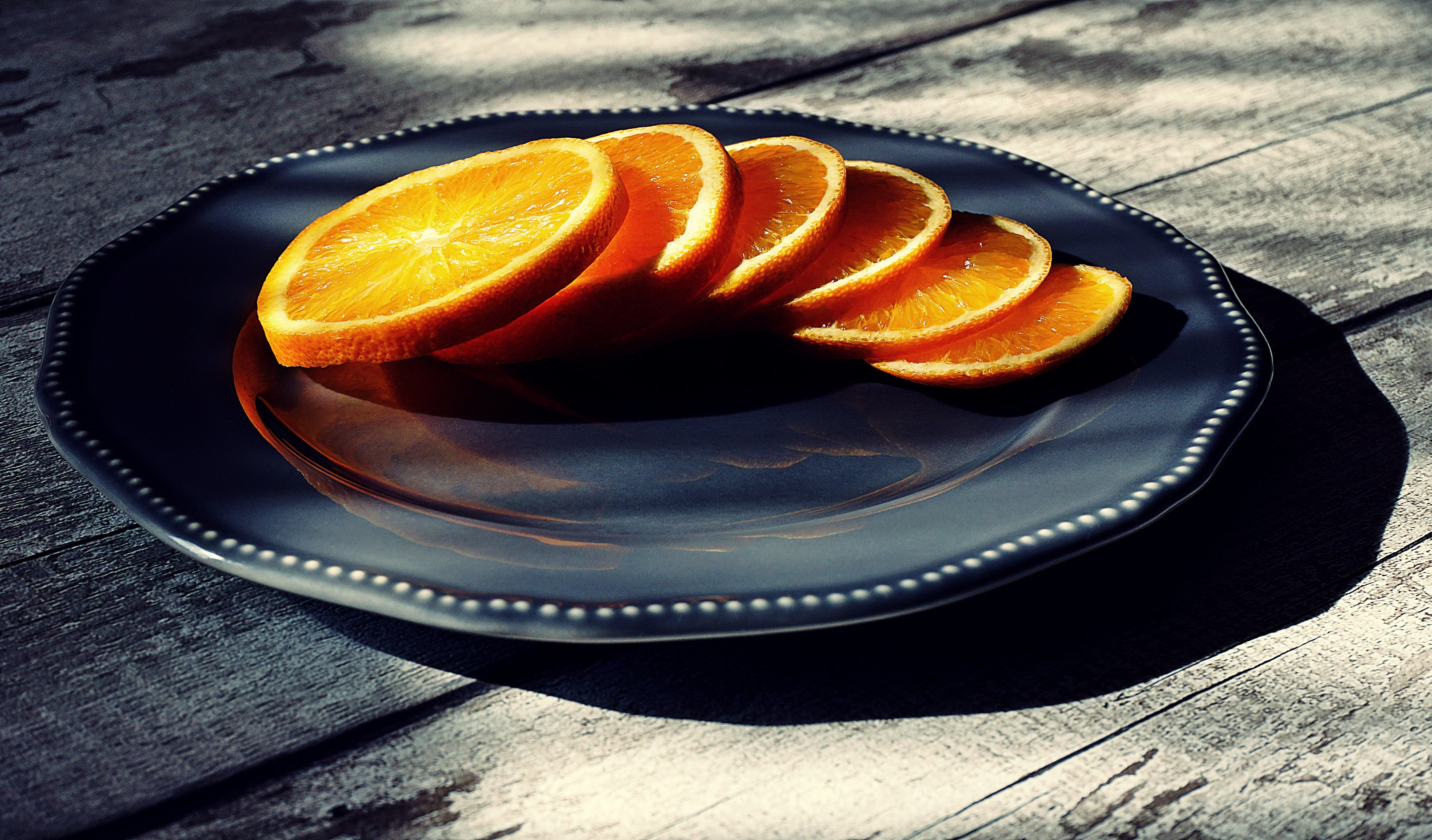 Six Slices of Oranges on Black Ceramic Plate