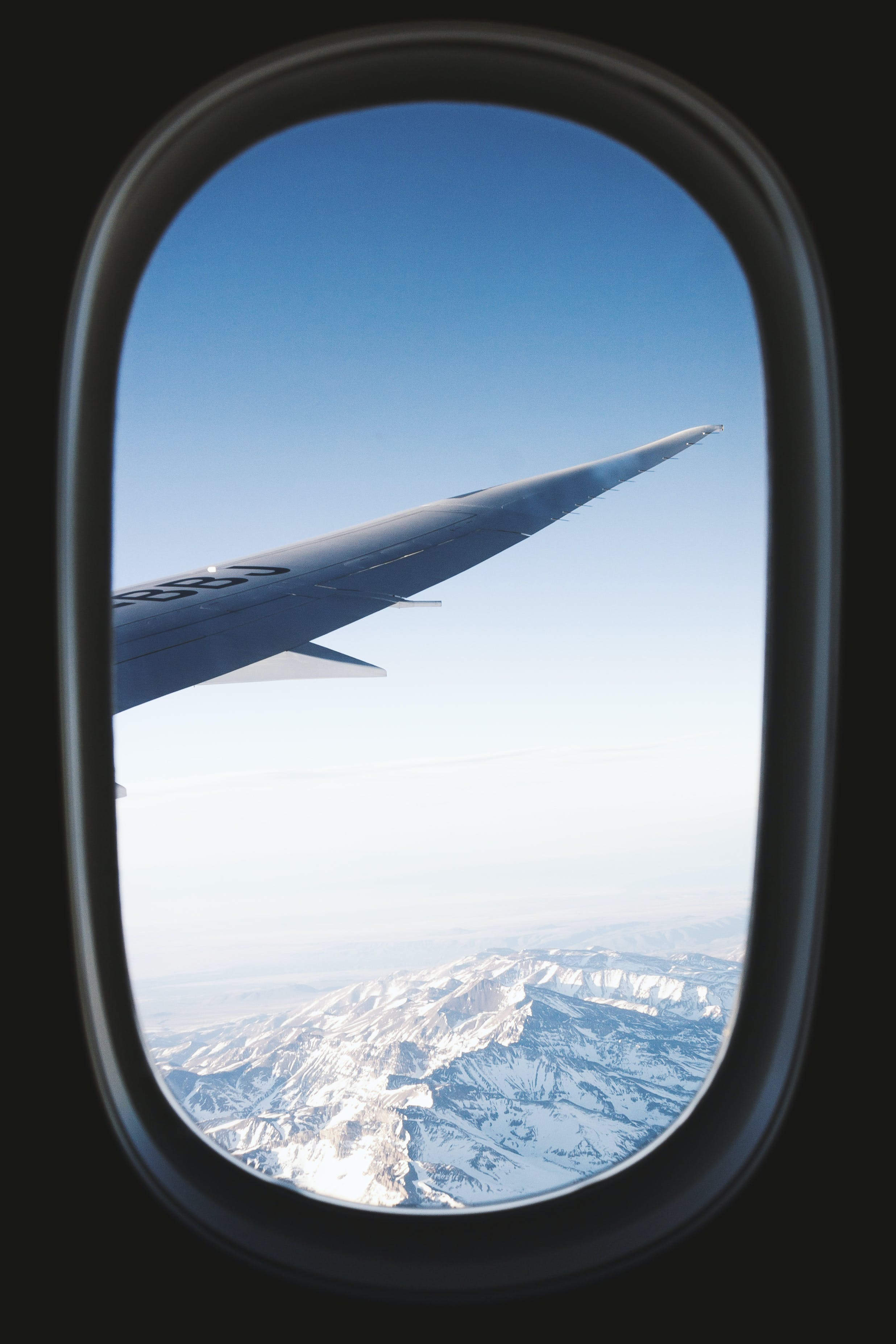 Gray Planes Right Wing With View of Snow-covered Mountains View from Window