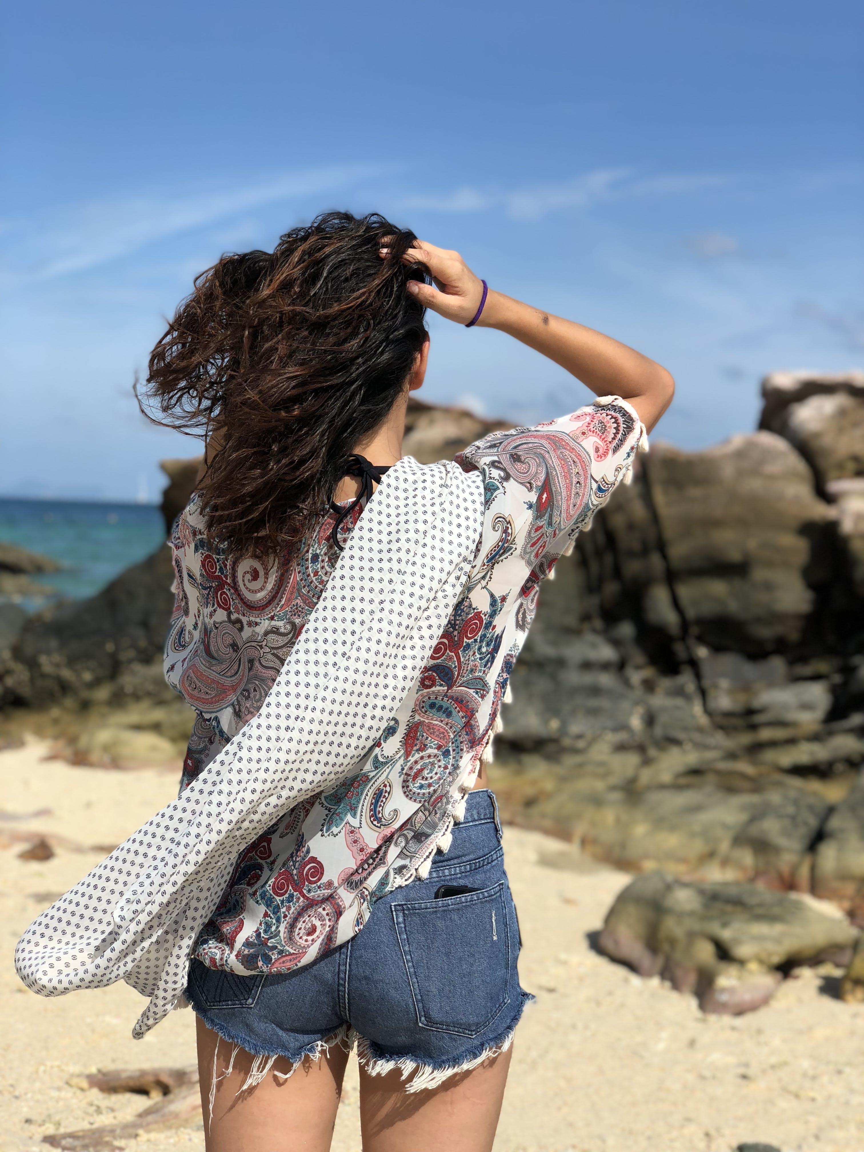 Woman Holding Her Hair Facing at Rock