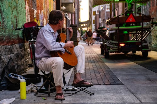 Man Sitting Playing Classical Guitar on Gray Road