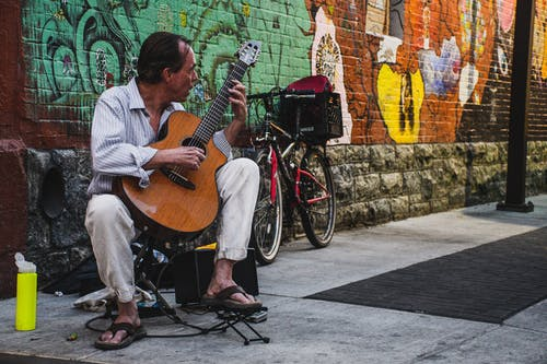 Man Seated and Playing Brown Classical Guitar on the Street