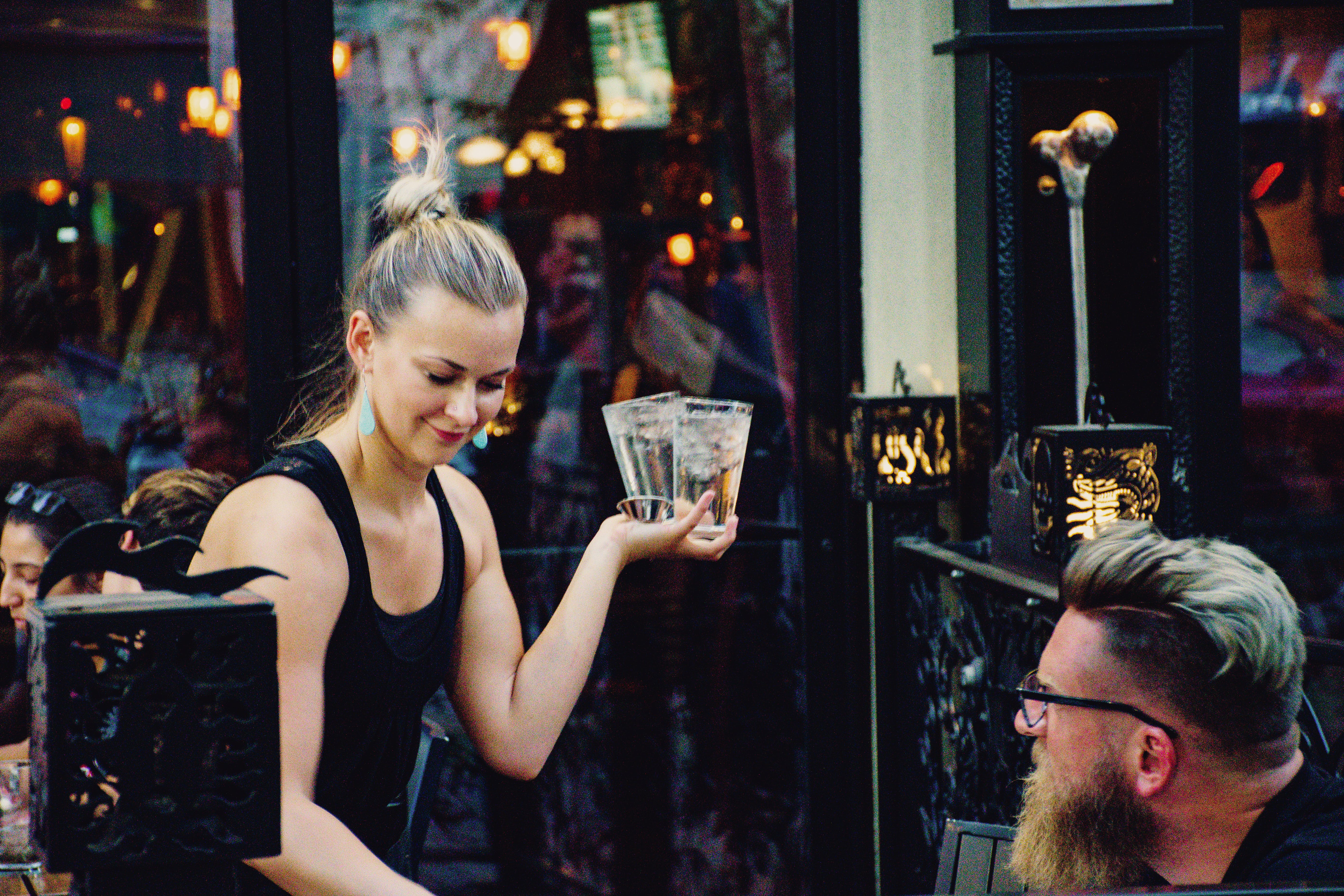 Woman Holding Higball Glass in Front of Man