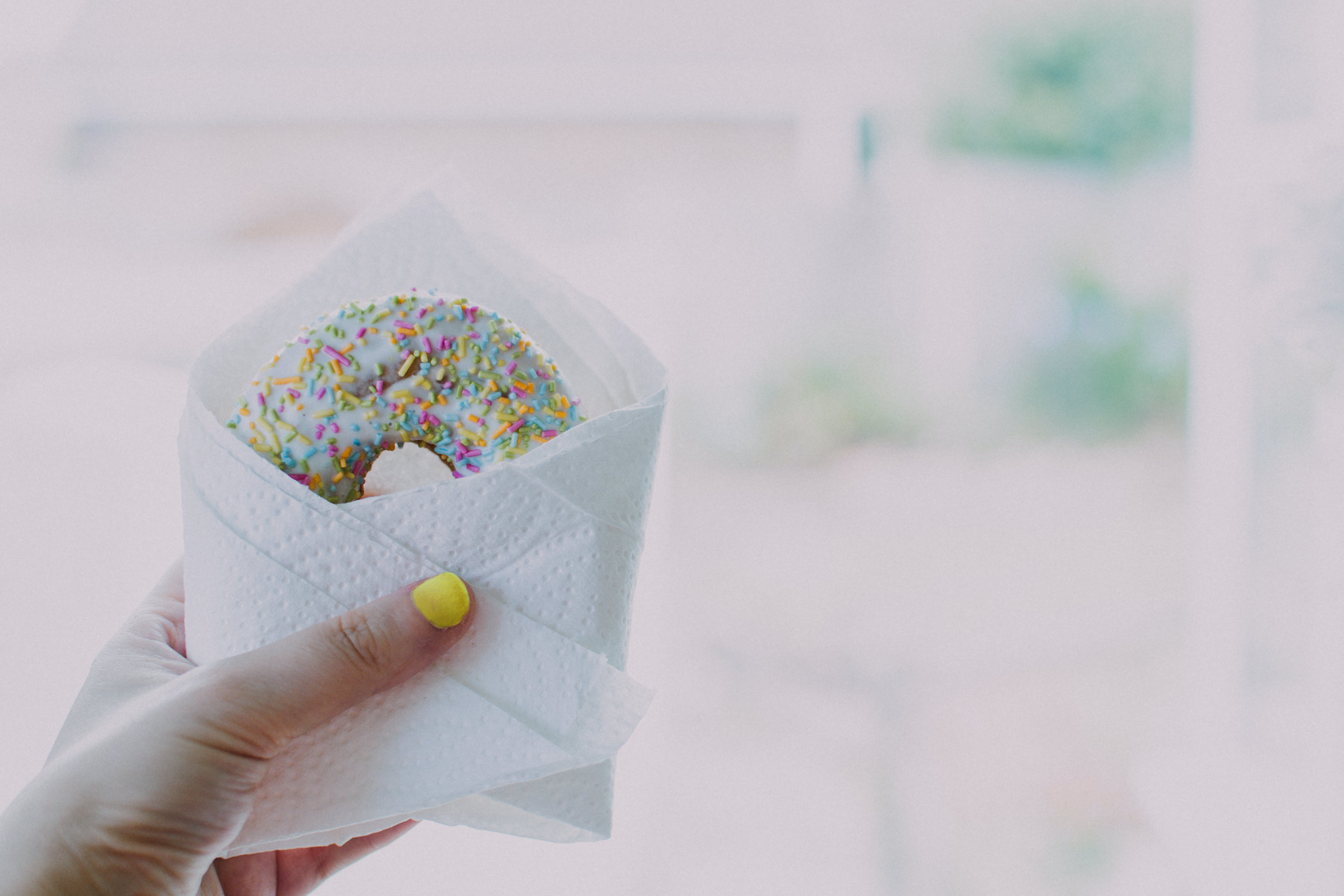 Woman Holding Doughnut With Sprinkles