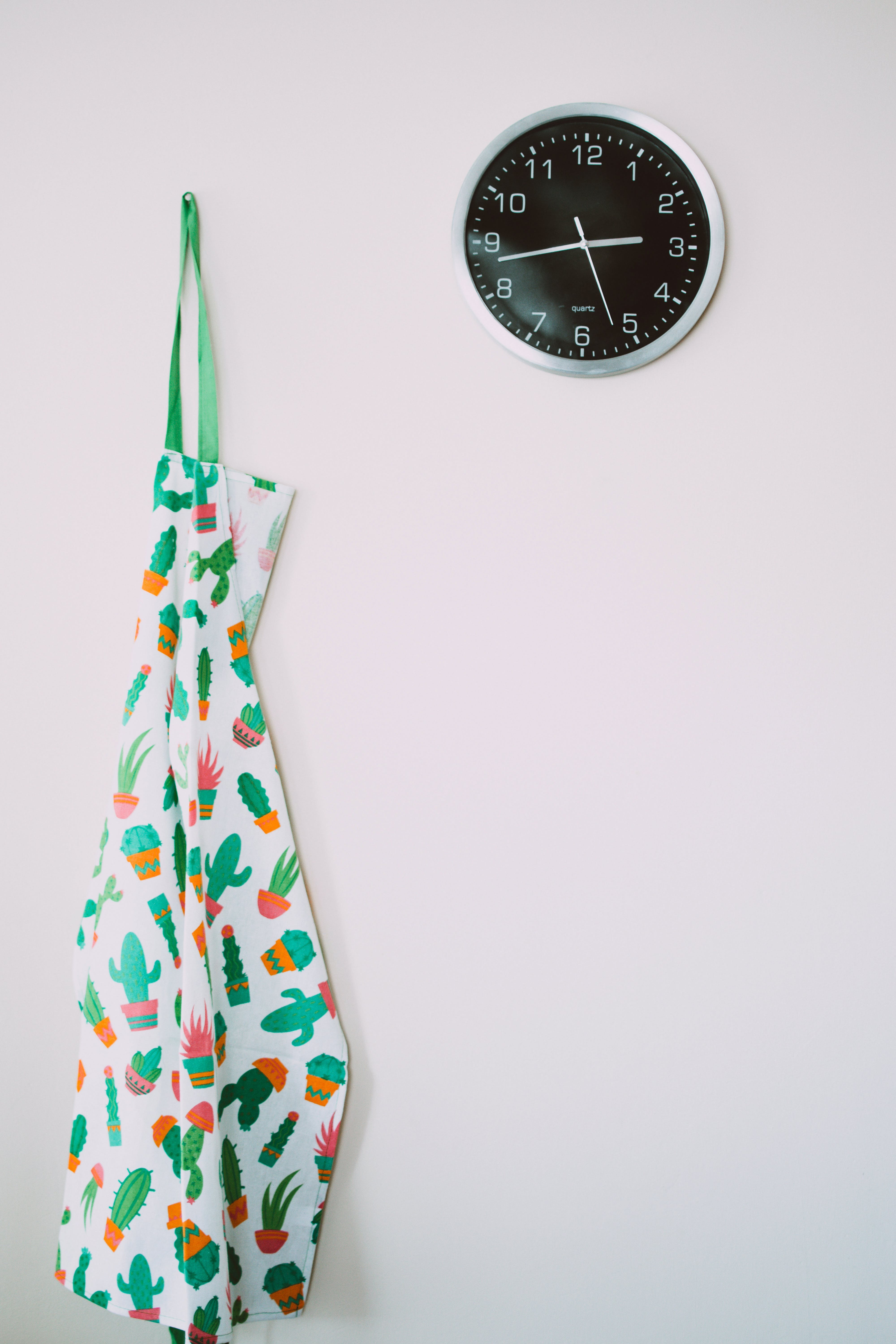 White and Green Cactus Pattern Apron Near Round Gray Analog Wall Clock