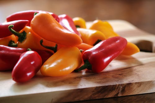Yellow and Red Peppers on Table
